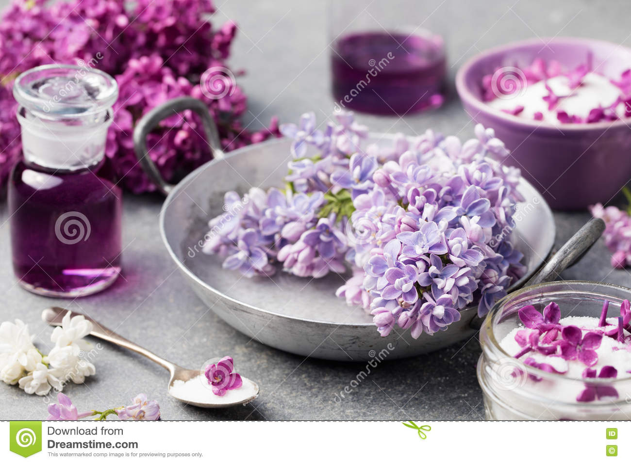 Lilac flowers sugar and syrup, essential oil with flower blossoms in glass jar Grey stone background
