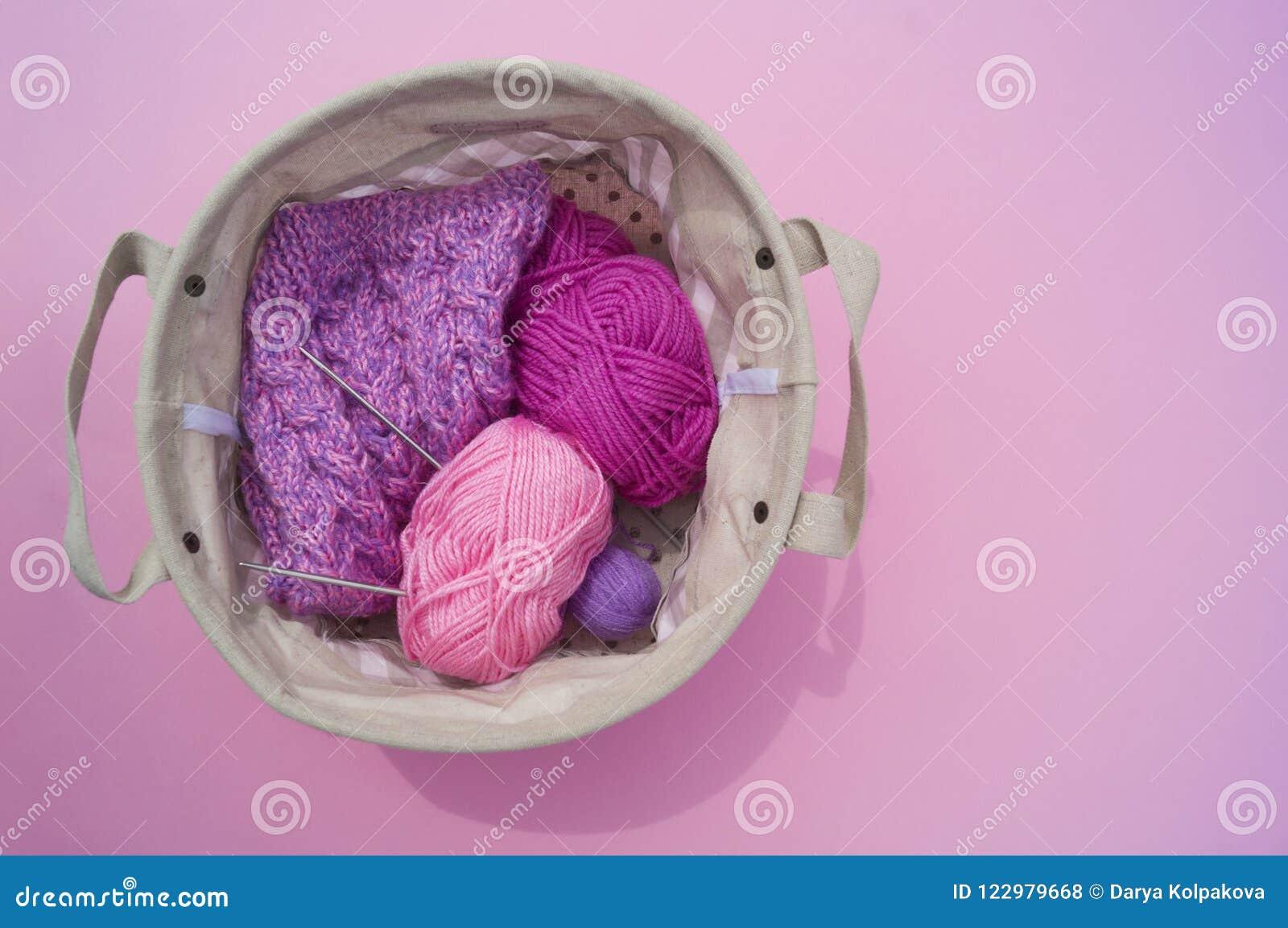 Lilac, roze en purpere verwarring van draden ligt in een mand op een roze achtergrond