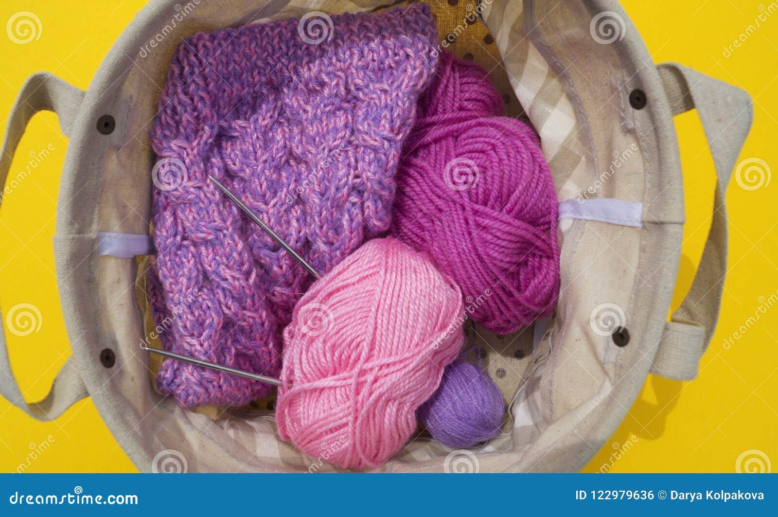 Lilac, roze en purpere verwarring van draden ligt in een mand op een gele achtergrond De favoriete hobby is creatief