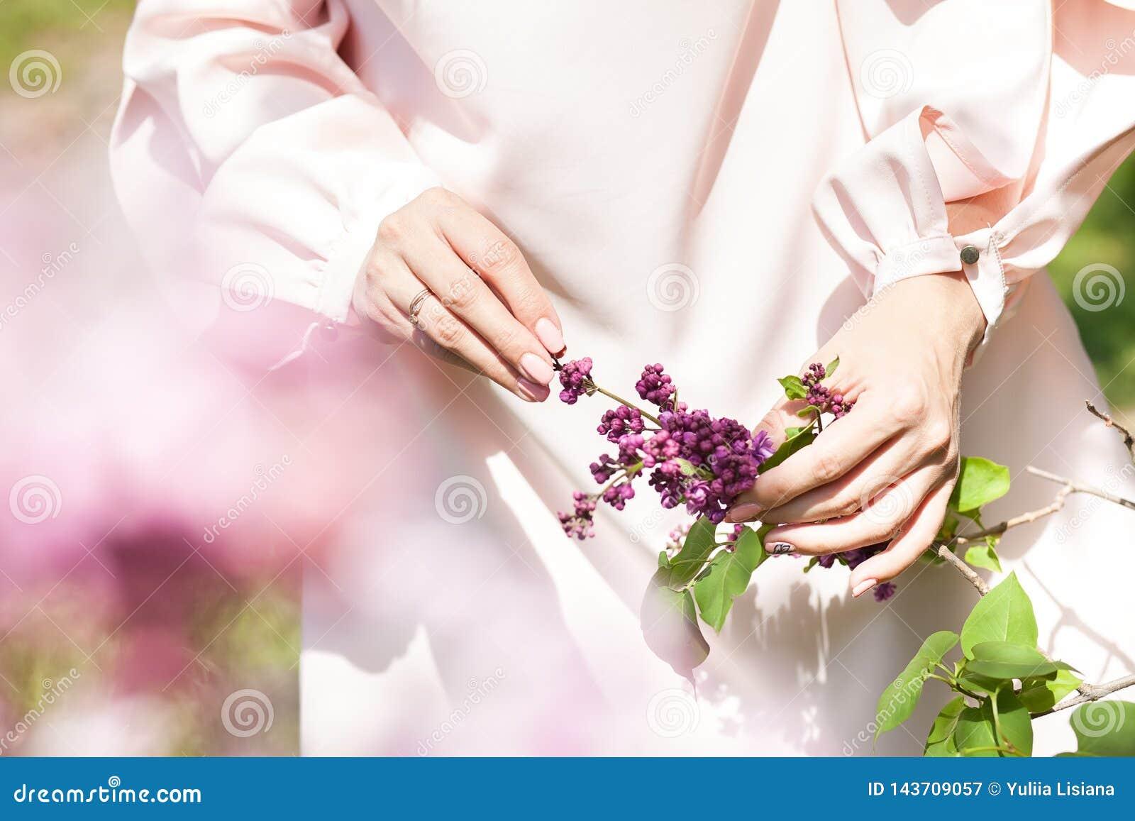 Lilan blommar i en hand på ett träd