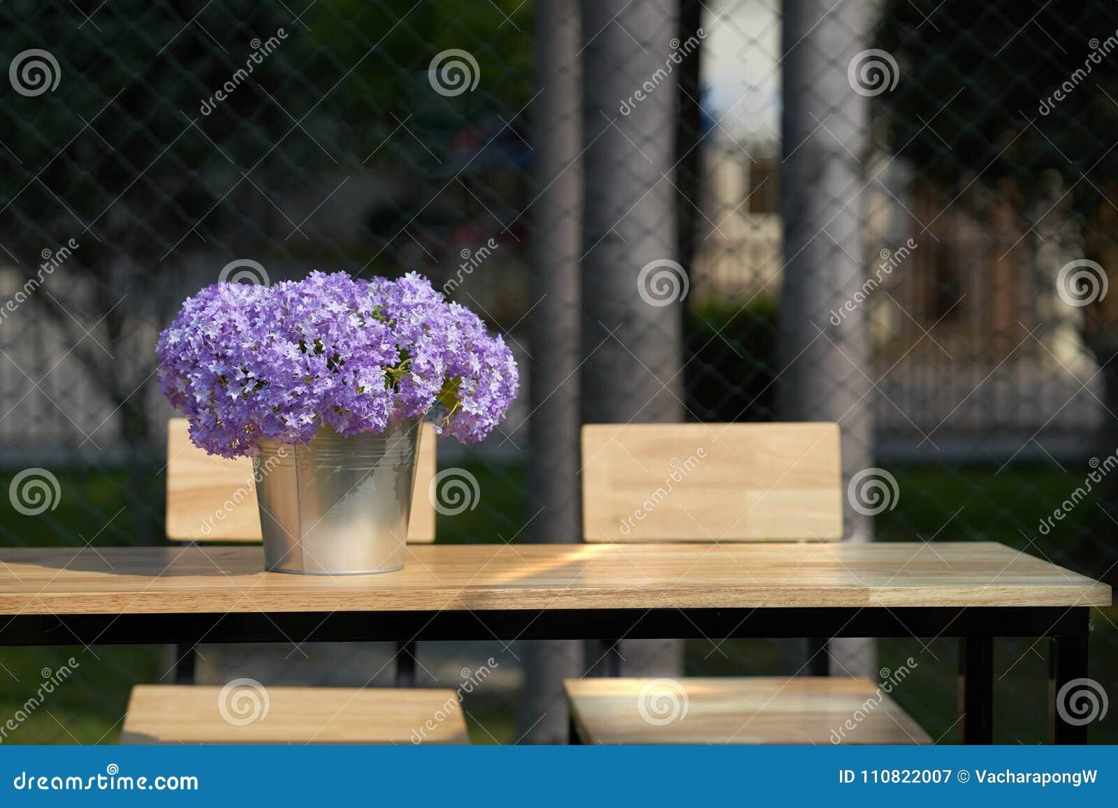 Lilan blommar i hinkvas på trätabellen med stolar med s