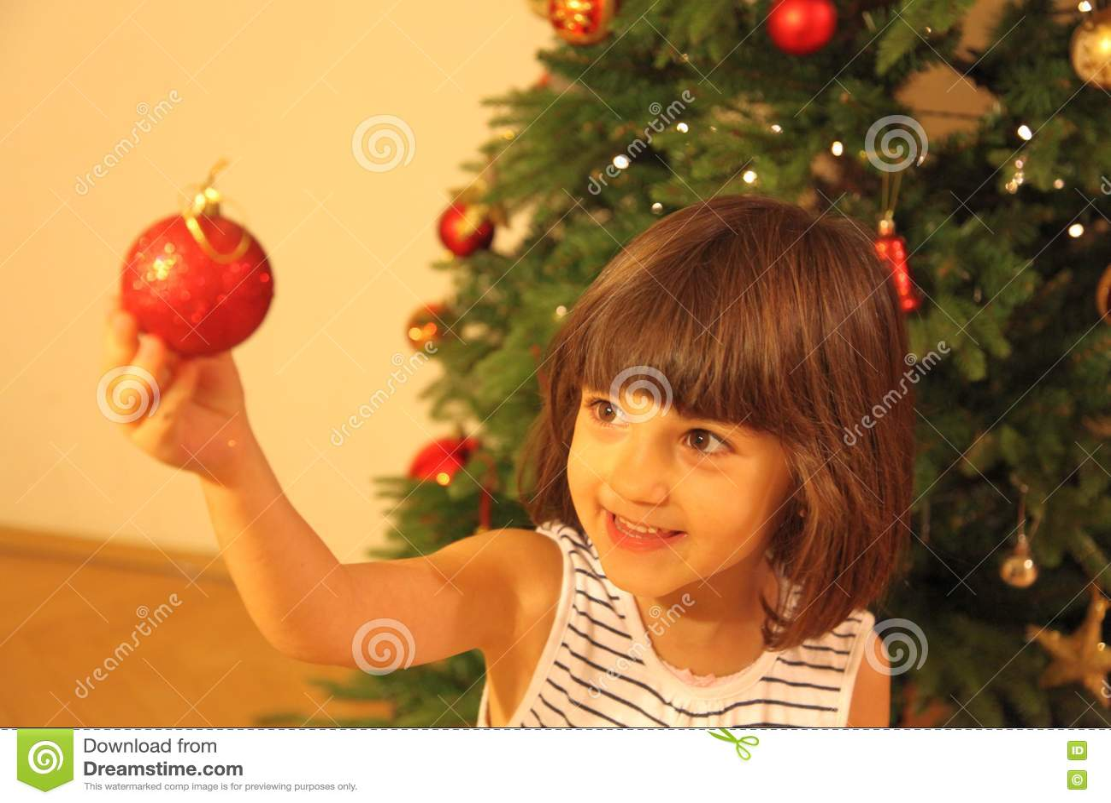 Lilla flickan dekorerar julgranen