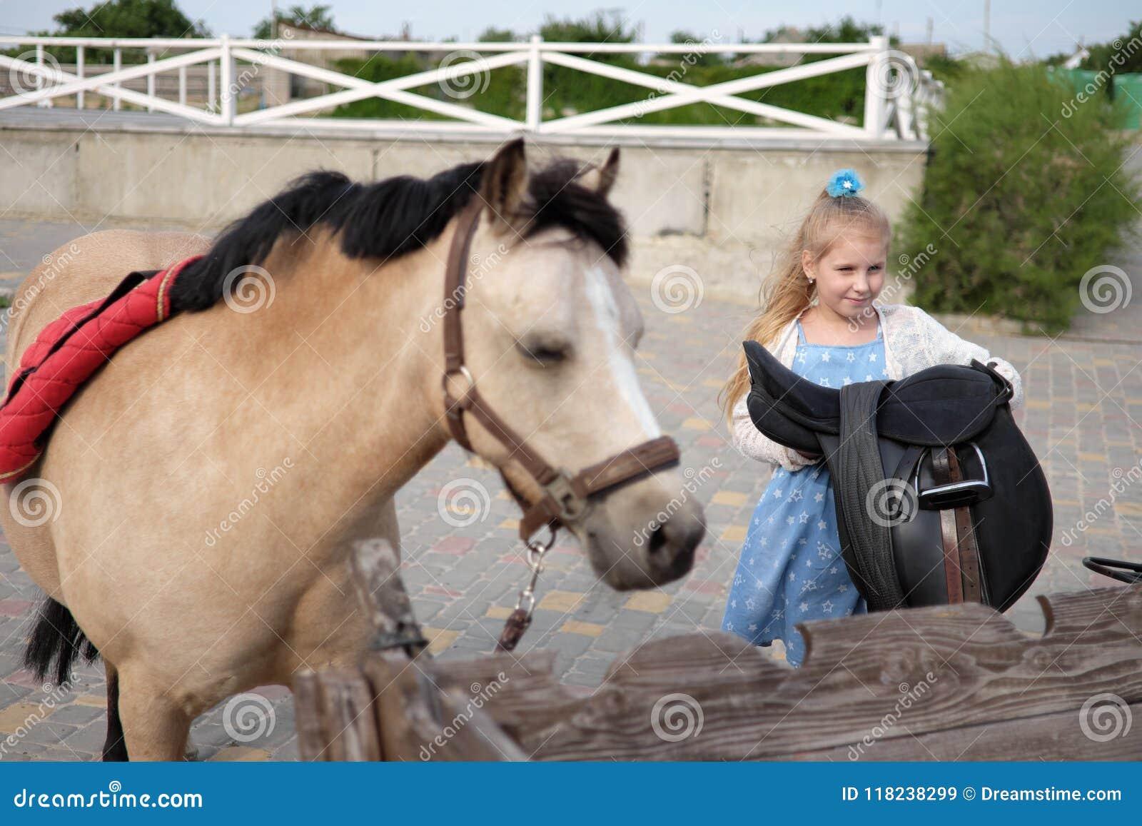Lilla flickan gör ren och kammar hennes ponny och sadlar honom
