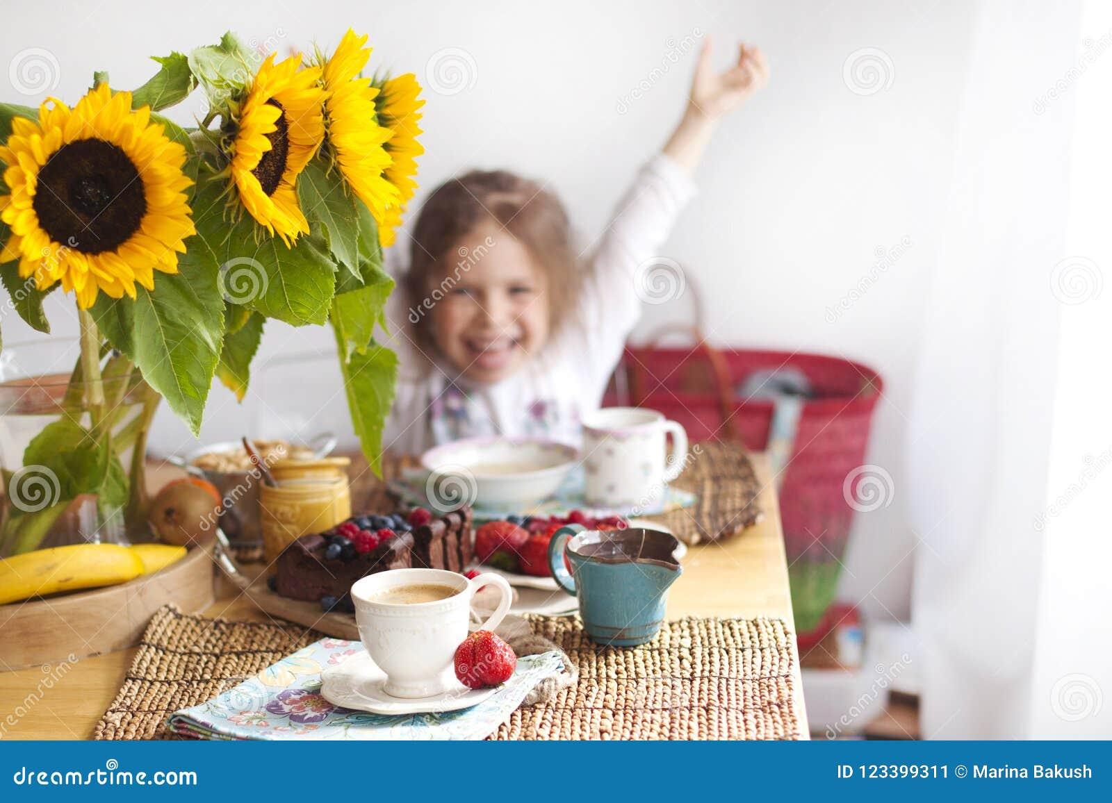 Lilla flickan har frukosten hemma På tabellen är en bukett av blommor av solrosor och en söt paj med frukt,
