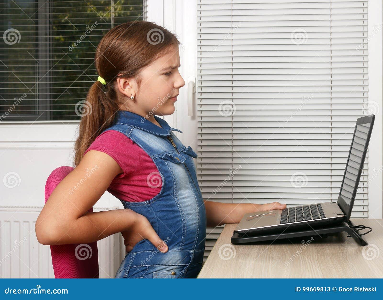 Lilla flickan har tillbaka att smärta, medan genom att använda en bärbar dator