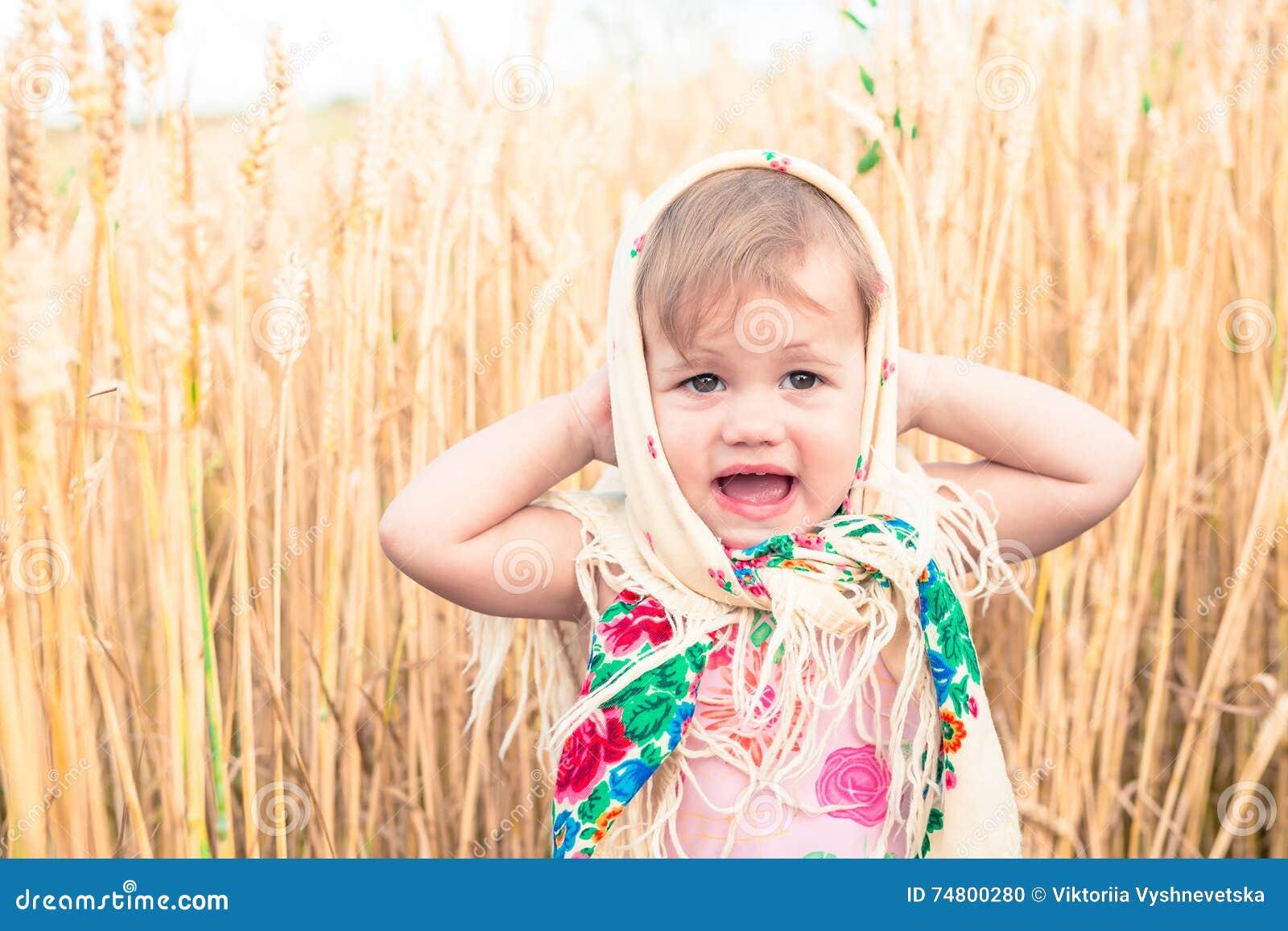267cd5a431ba Lilla flickan i halsduk står i mitt av fältet och gråter Föräldralöers  sociala problem