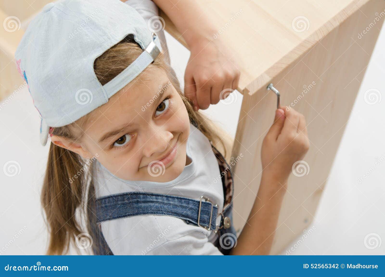 Lilla flickan i klänningsamlaremöblemang drar åt skruvar Allen