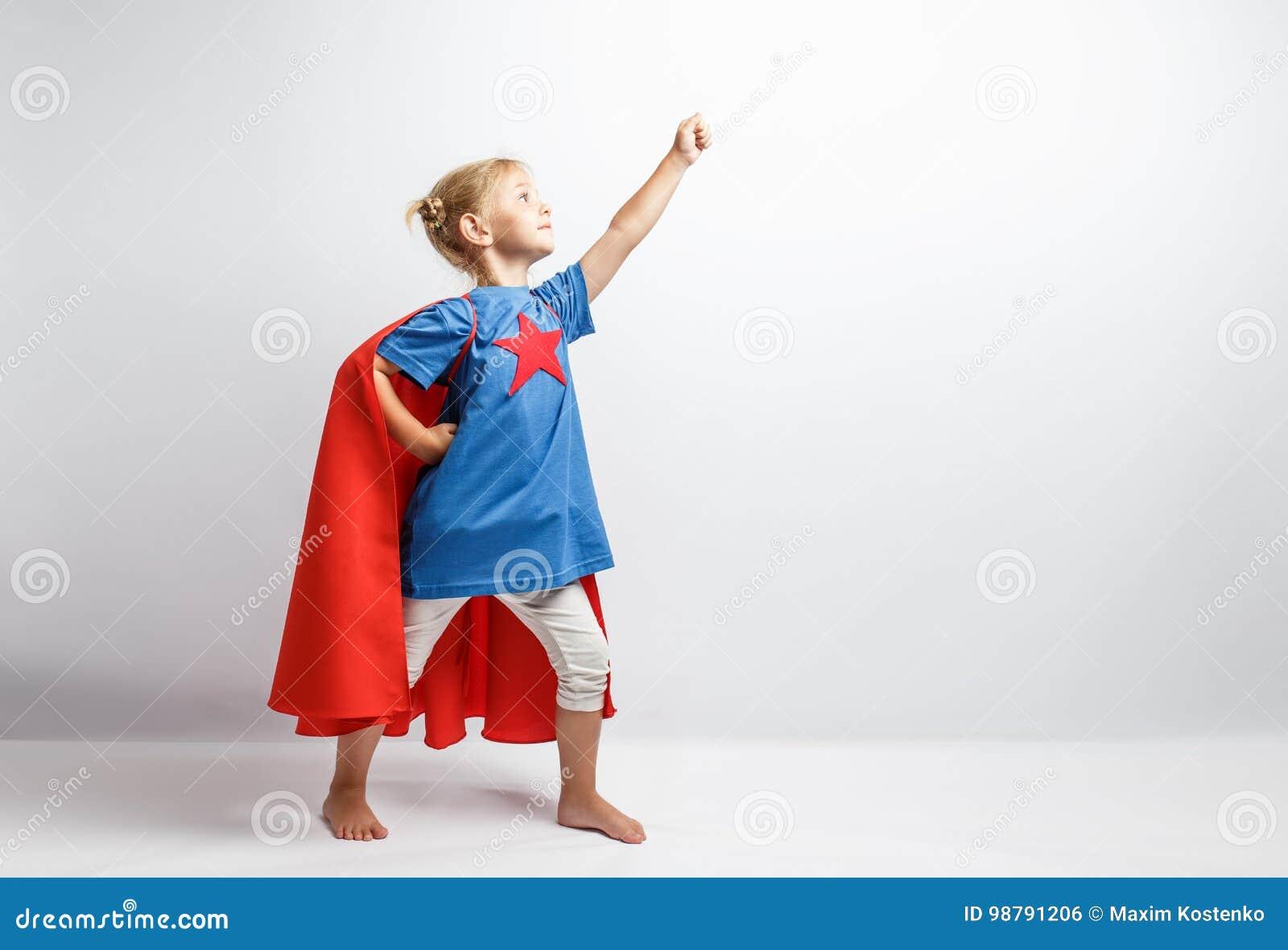 Lilla flickan klädde som superheroen som tillsammans med står den vita väggen