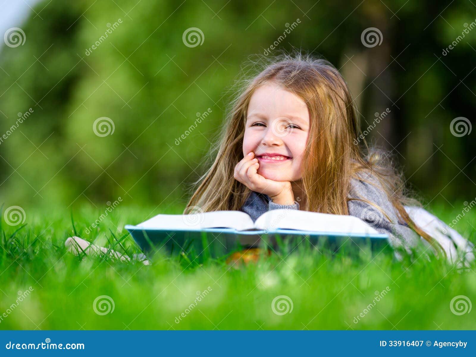 Lilla flickan läser boken på gräset