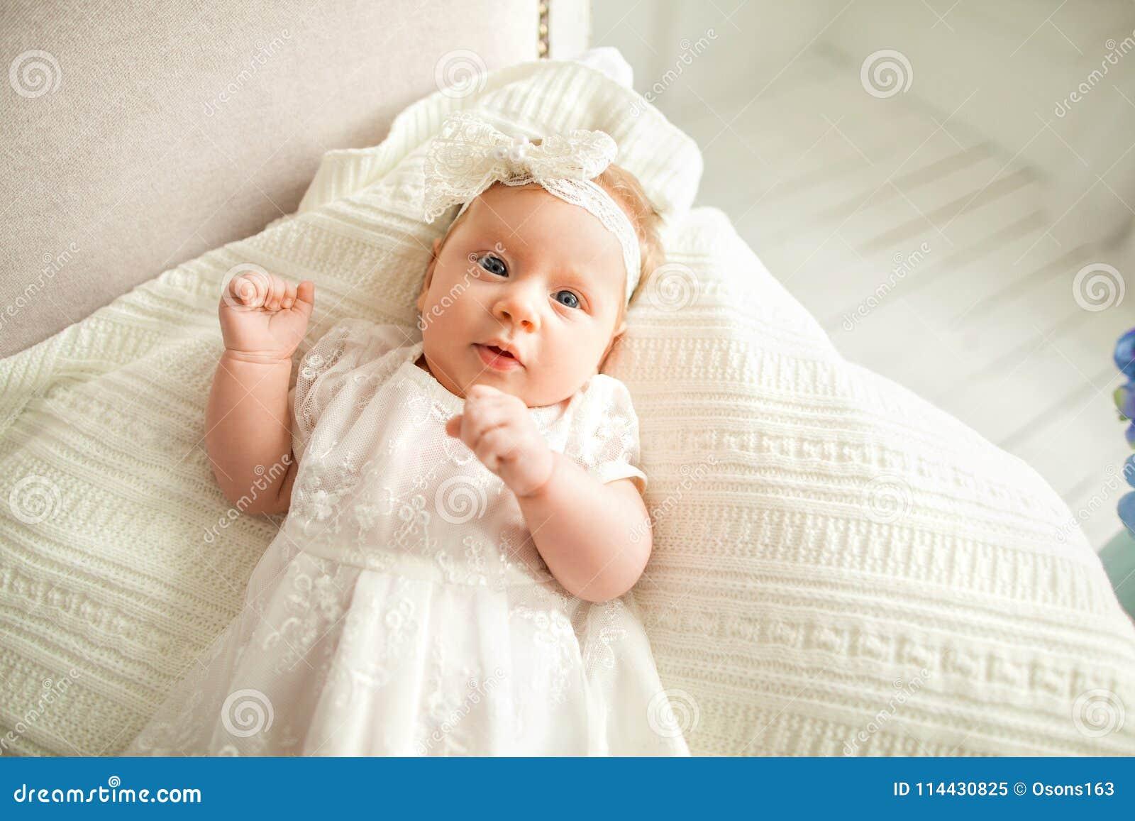 Lilla flickan med en vit pilbåge ligger på soffan, på en vit backg