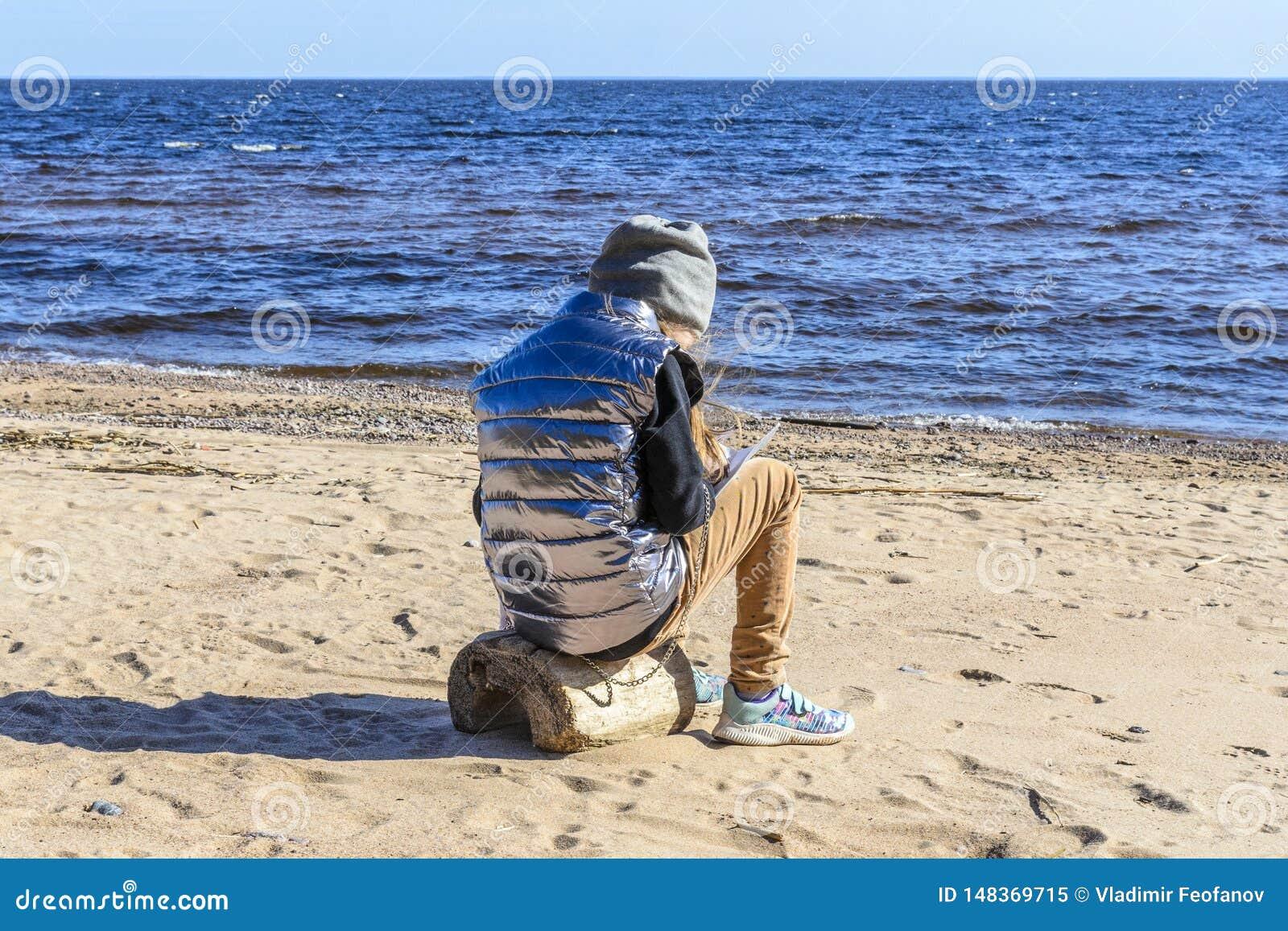 Lilla flickan på stranden, mot bakgrunden av stenar, sand och härliga vågor av havet och oväsenet av vinden, sitter a