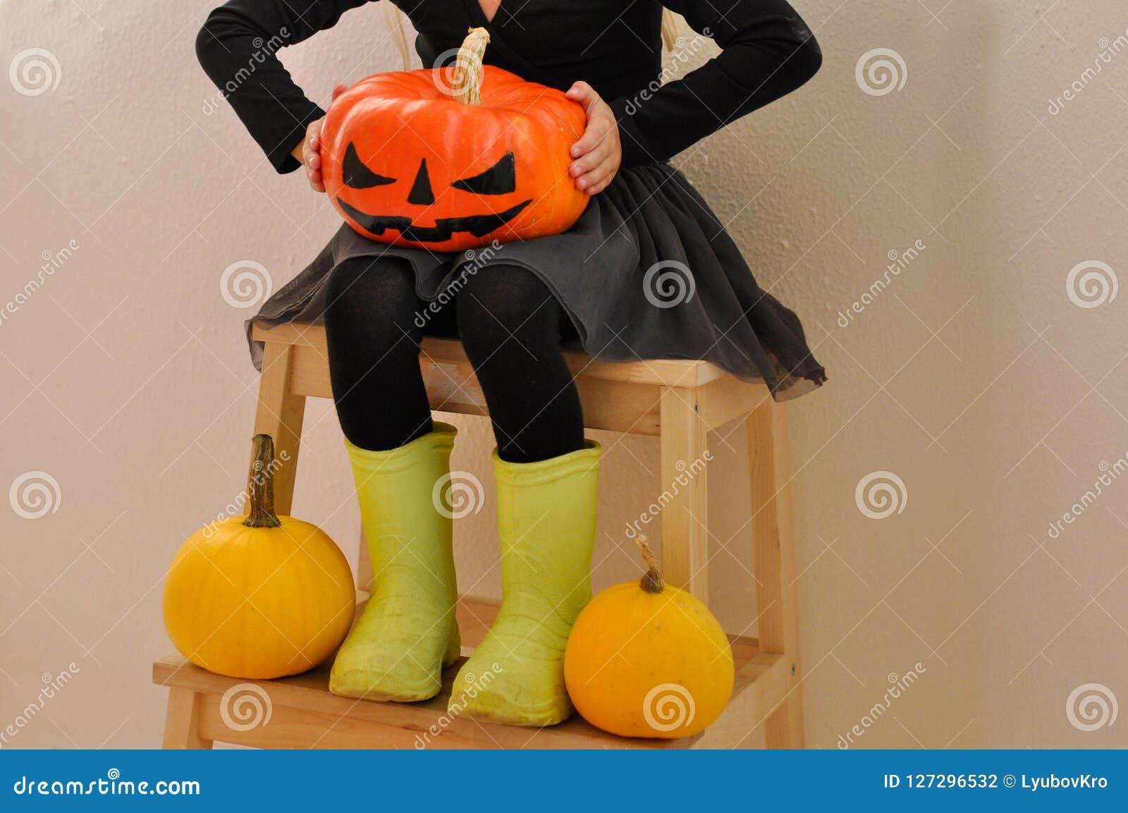 Lilla flickan rymmer en läskig pumpa för allhelgonaafton som sitter på en bänk som omges av andra pumpor Closup
