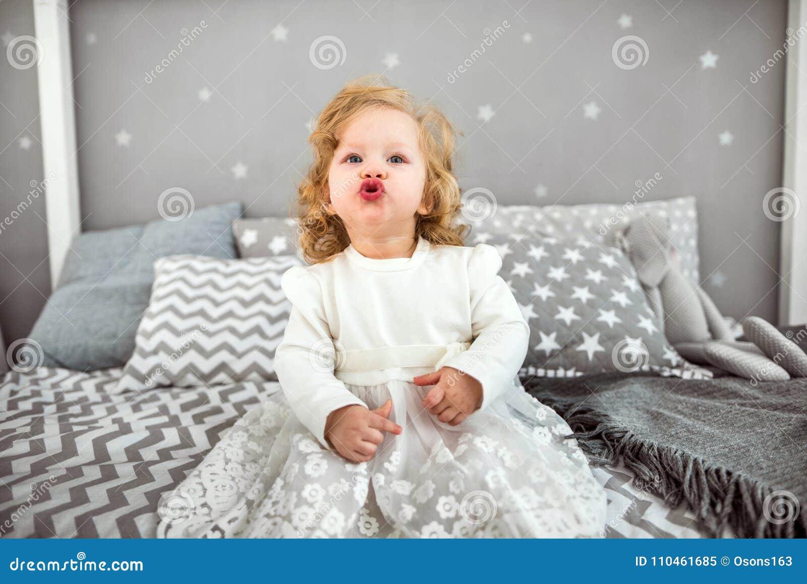 Lilla flickan sitter på sängen