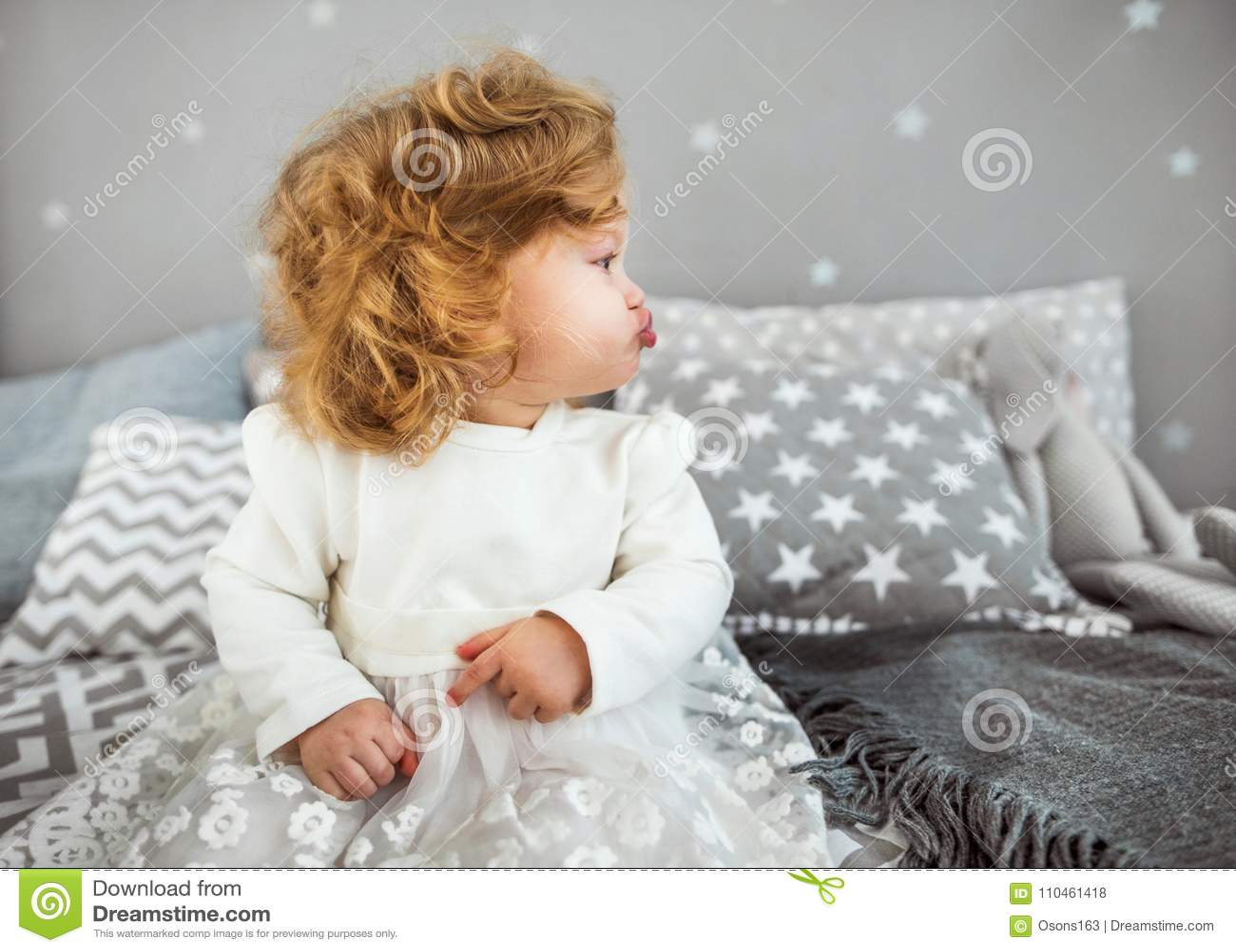 Lilla flickan sitter på sängen med hennes leksak