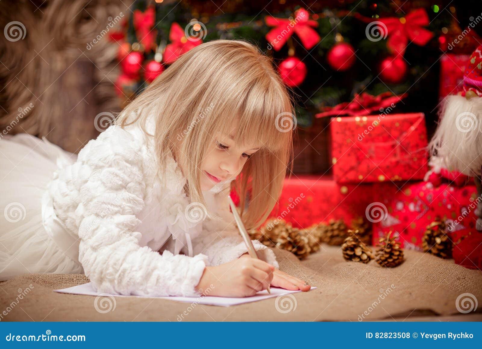 Lilla flickan skrivar ett brev till Santa Claus