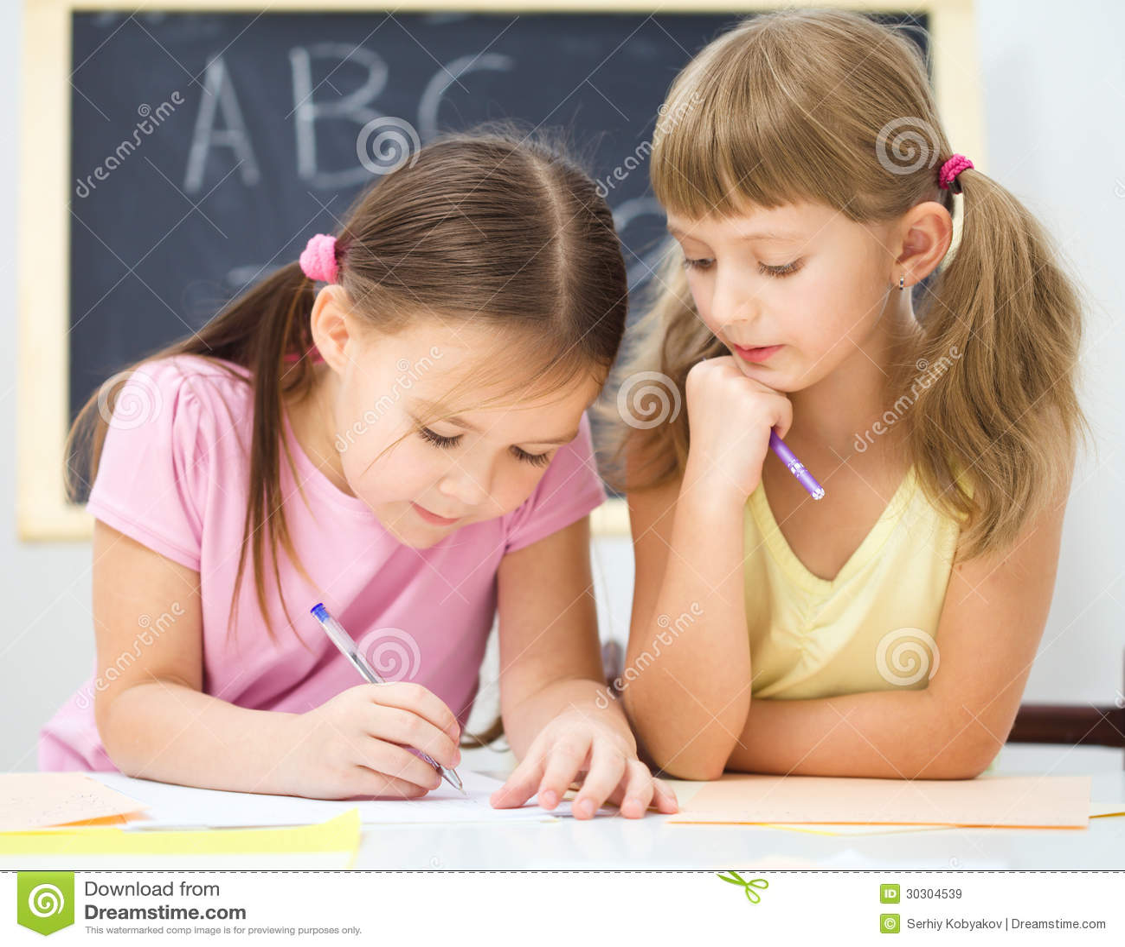 Lilla flickan skriver genom att använda en penna