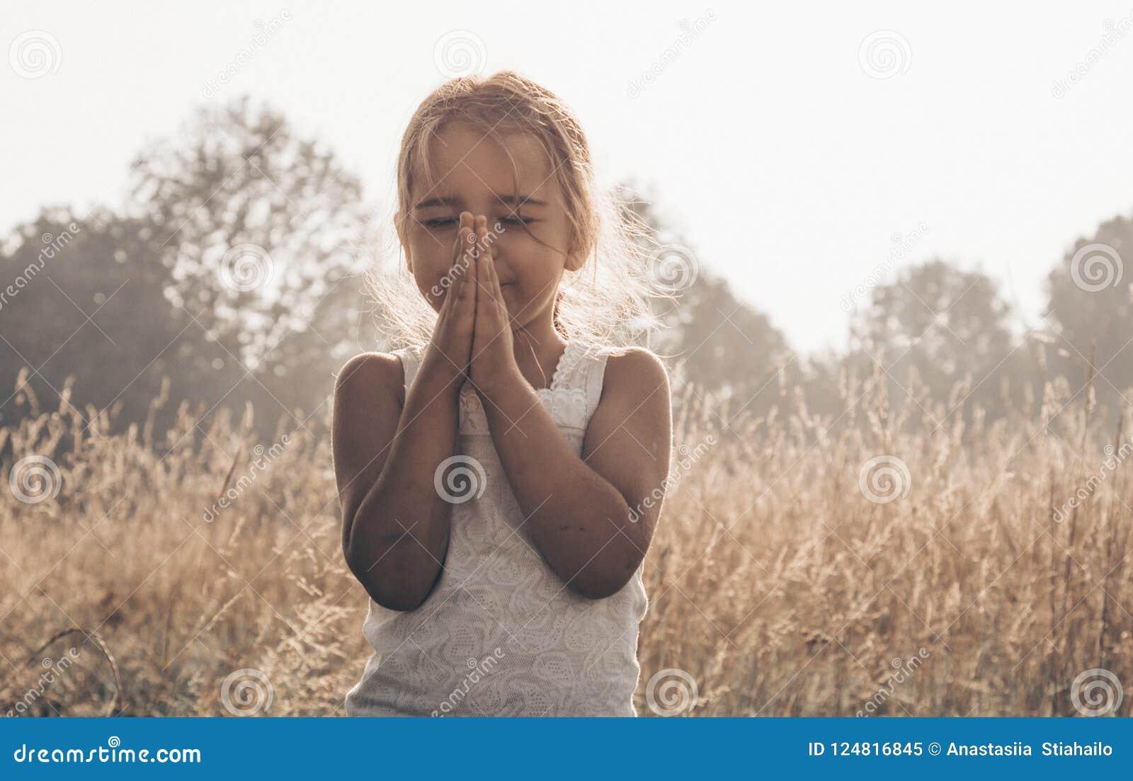 Lilla flickan stängde henne ögon som ber på solnedgången Händer vek i bönbegreppet för tro, andlighet och religion Hopp begrepp