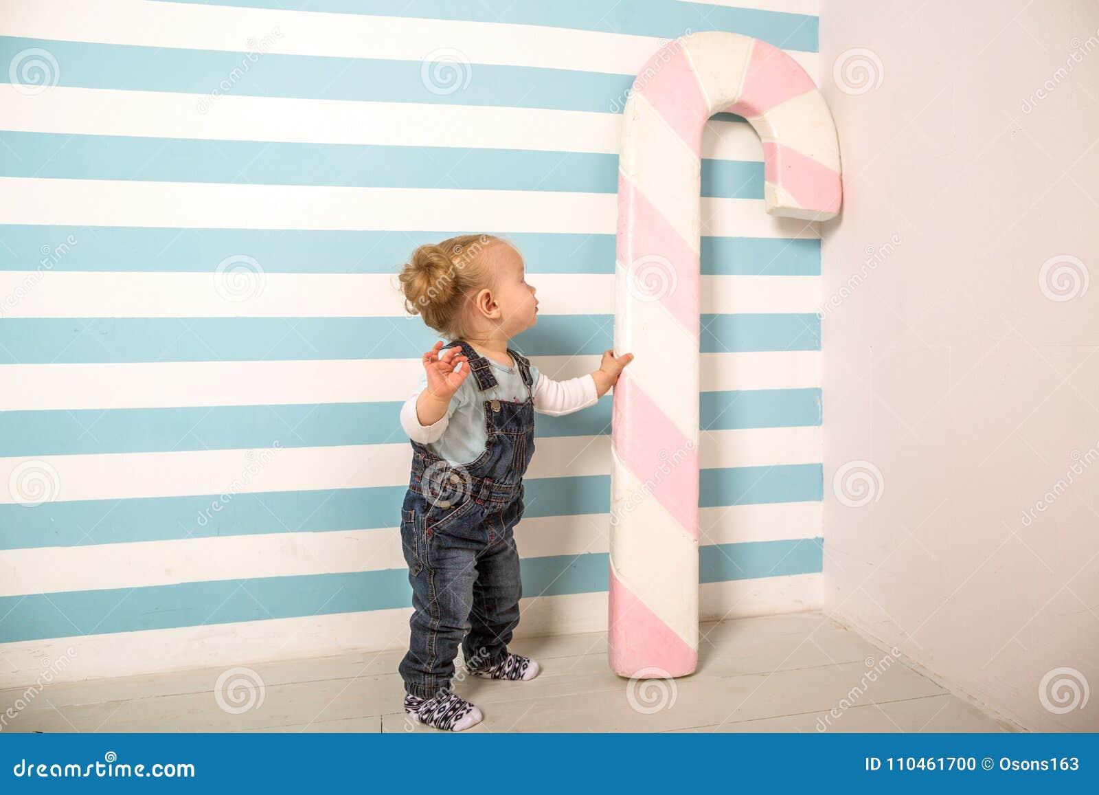 Lilla flickan står nära en randig bakgrund med en stor godis