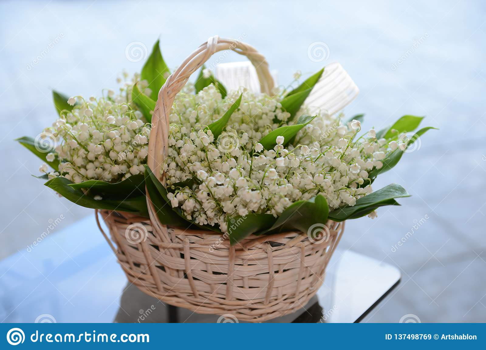 Lily the valley, a bouquet of lilies in a basket on a light blue background