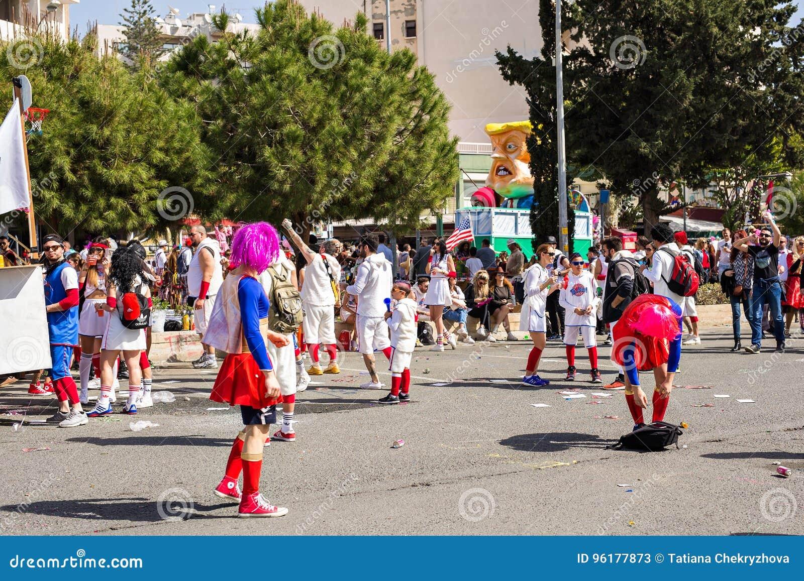 LIMASSOL CYPERN - FEBRUARI 26: Carnivalists i hattar för en silvercylinder följer joyfully den Limassol kommunmusikbandet