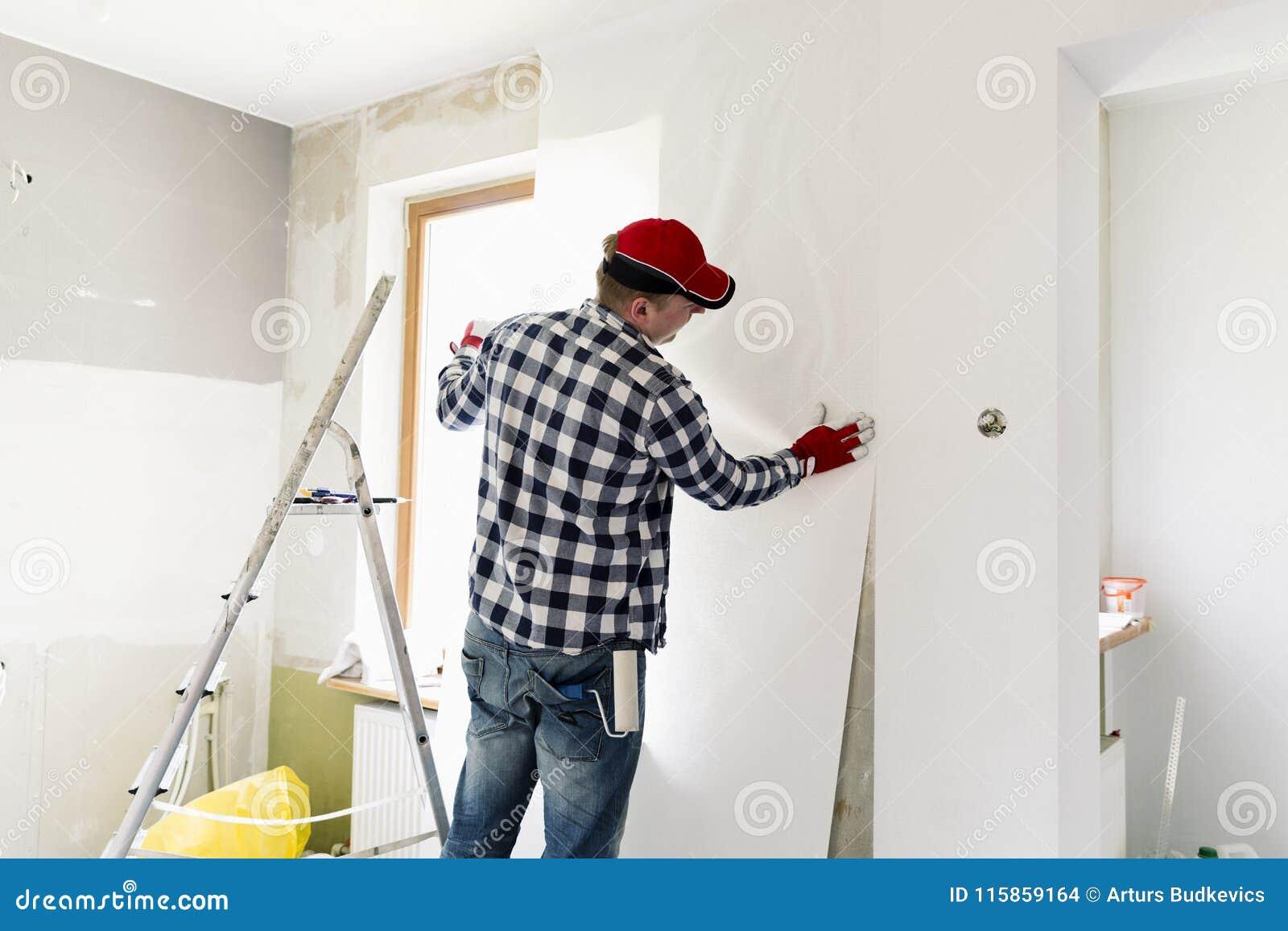 Limma hemmastadda tapeter Den unga mannen, arbetare är uppställningtapeter på väggen Hem- renoveringbegrepp