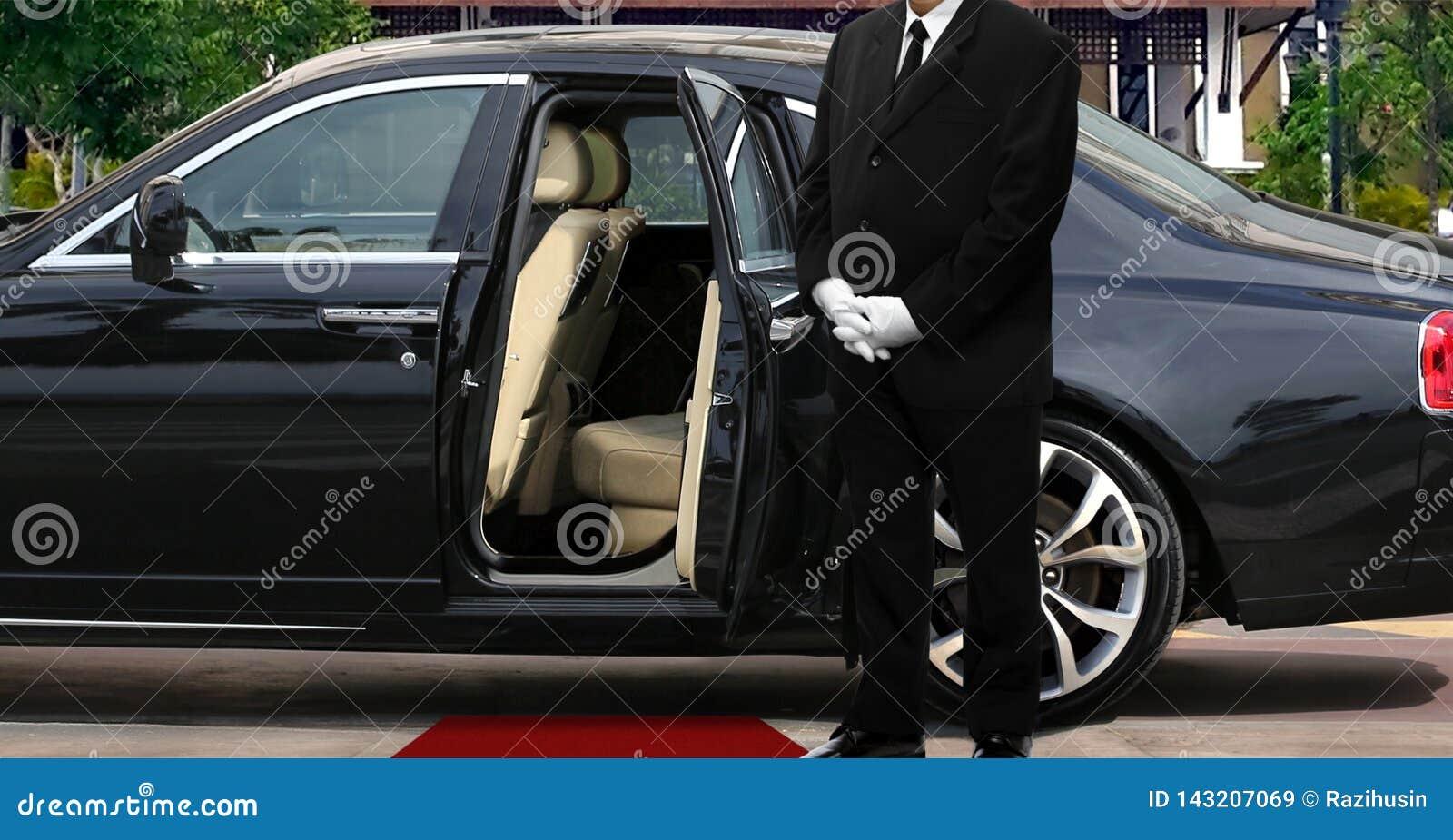 Limo kierowcy pozycja obok rozpieczętowanego samochodowego drzwi z czerwonym chodnikiem