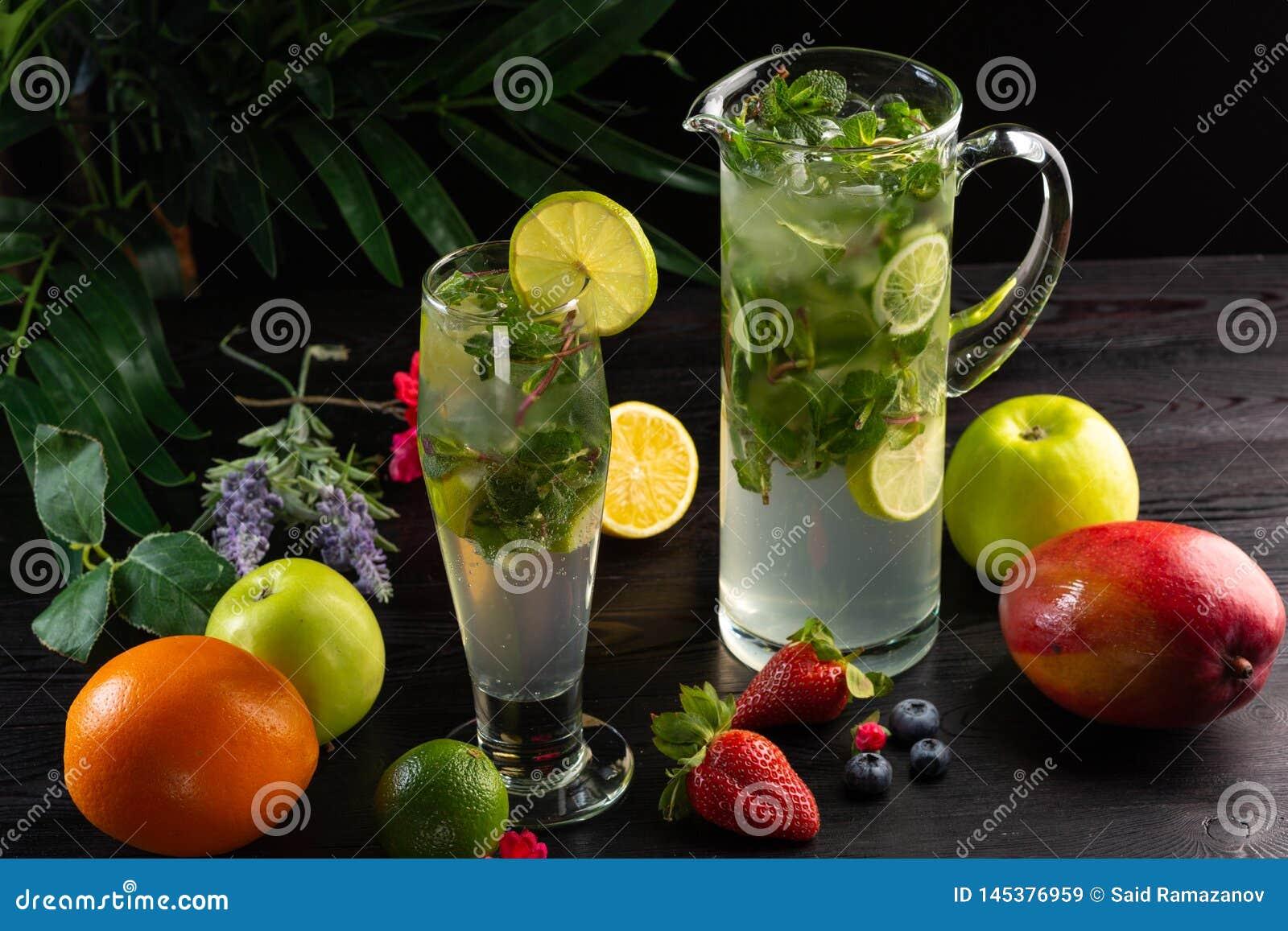Limonada de Mojito en un jarro y un vidrio y frutas en un fondo de madera oscuro