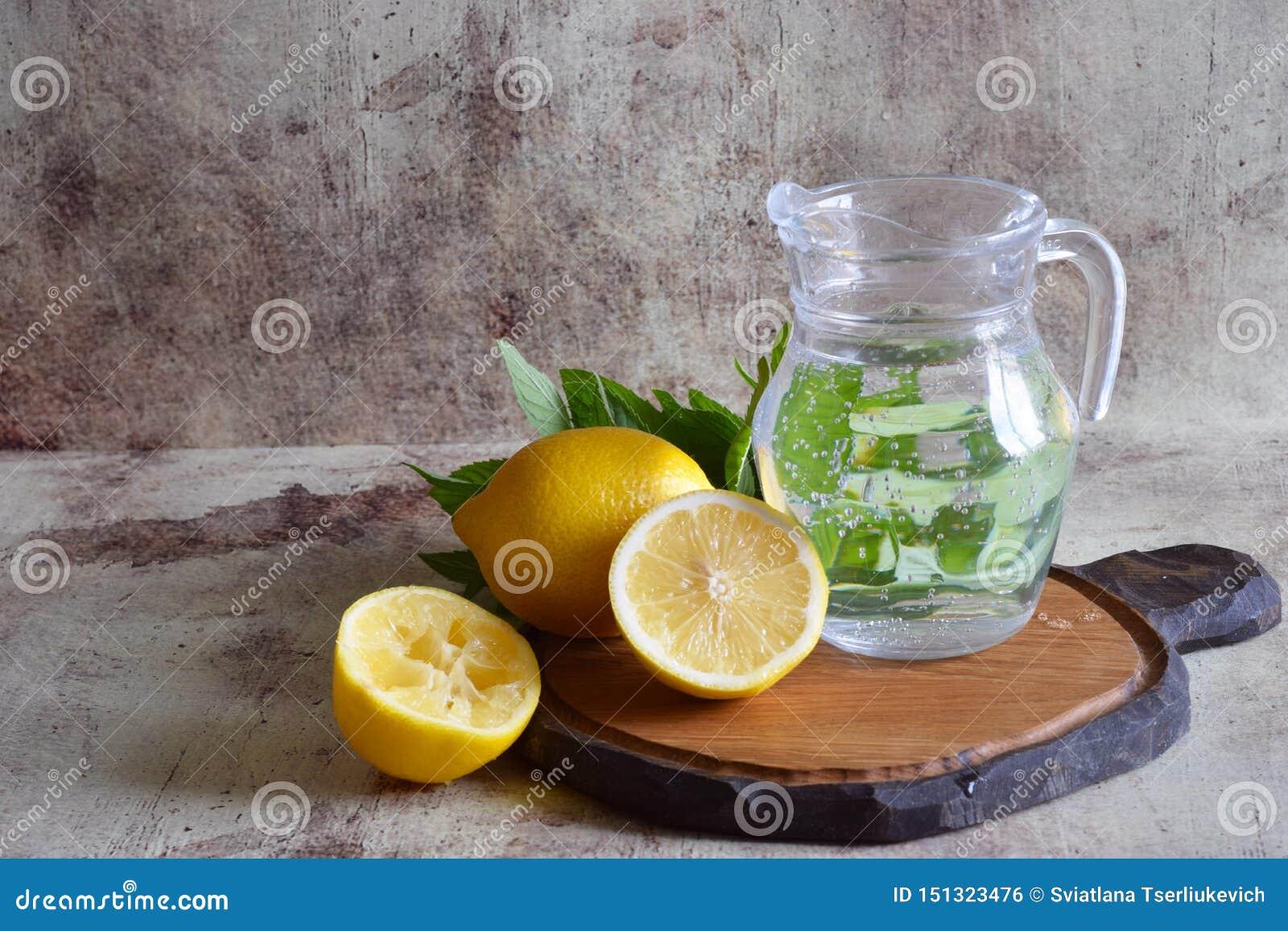 Limonada de refrescamento em um filtro bonito, limões, ramos perfumados da hortelã na tabela