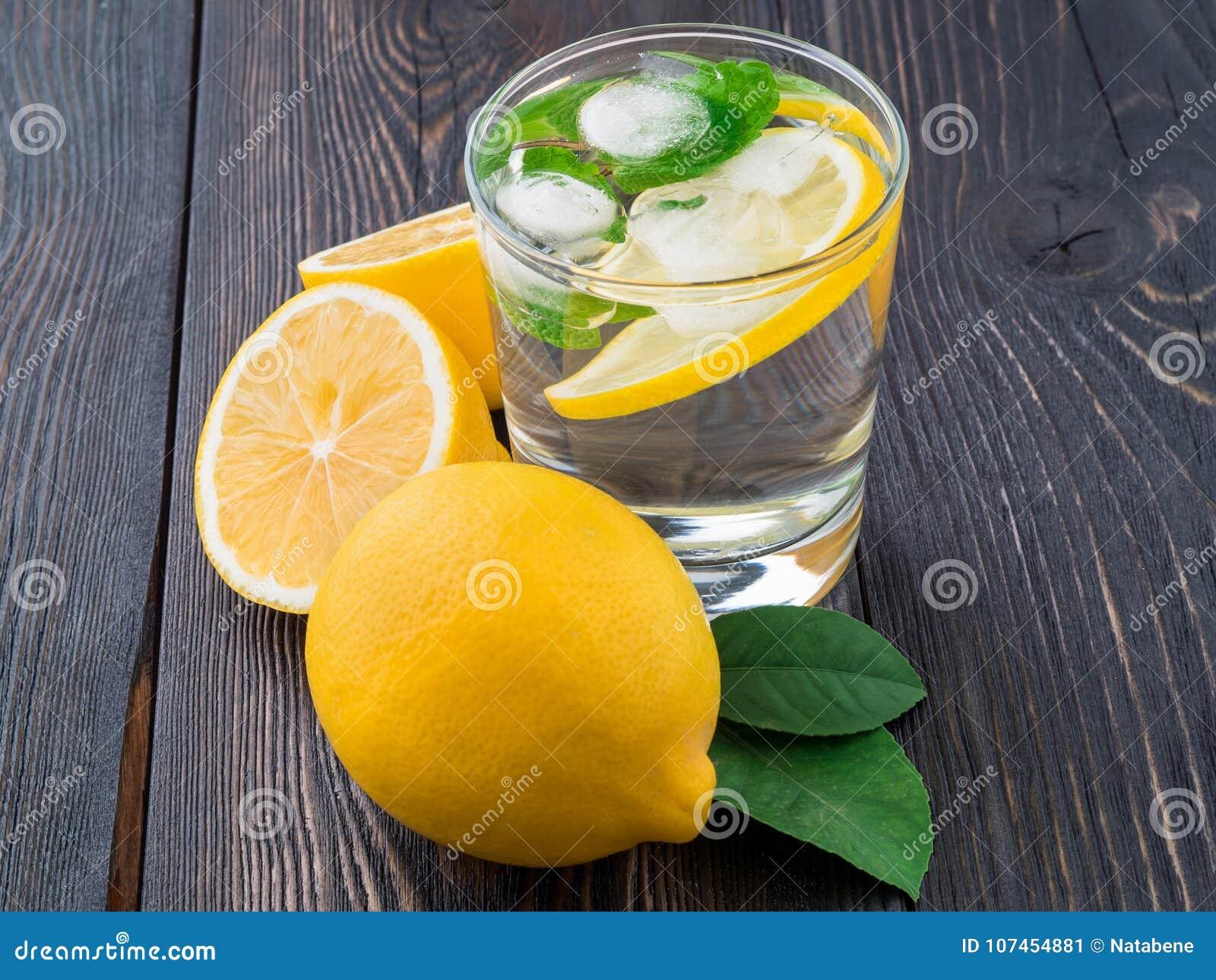 Limonada en un vidrio, un limón medio, hojas frescas en el marrón oscuro wo