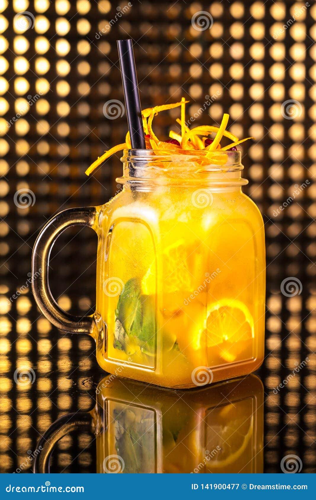 Limonade jaune de macédoine de fruits avec le citron frais dans le pot de cru