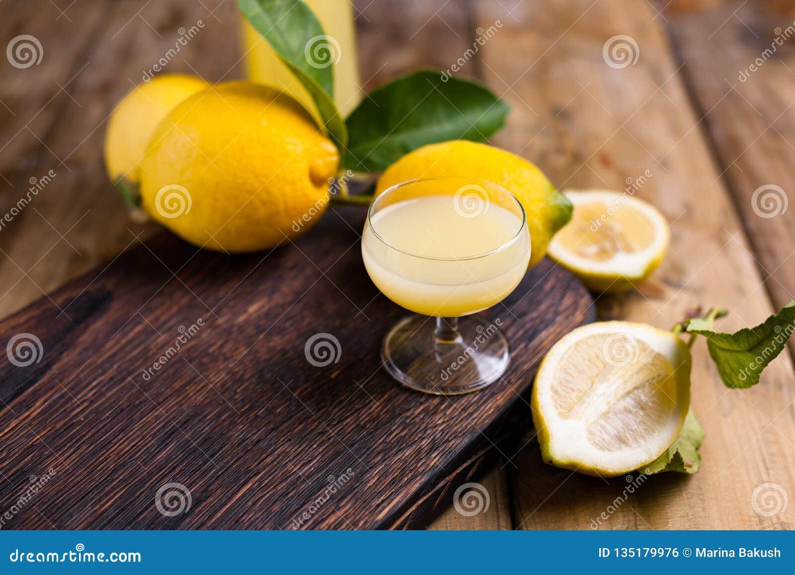 Limoncello и лимоны на деревянной доске Традиционный алкоголь