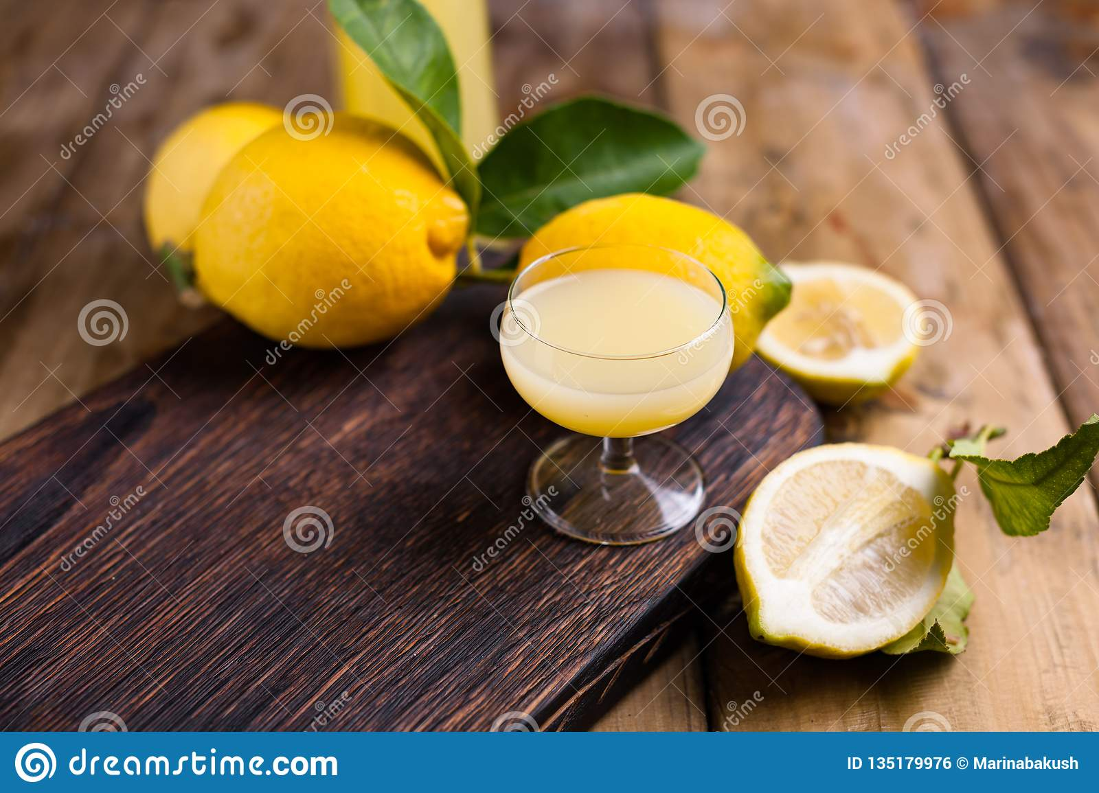 Limoncello and lemons on a wooden board. The traditional alcohol