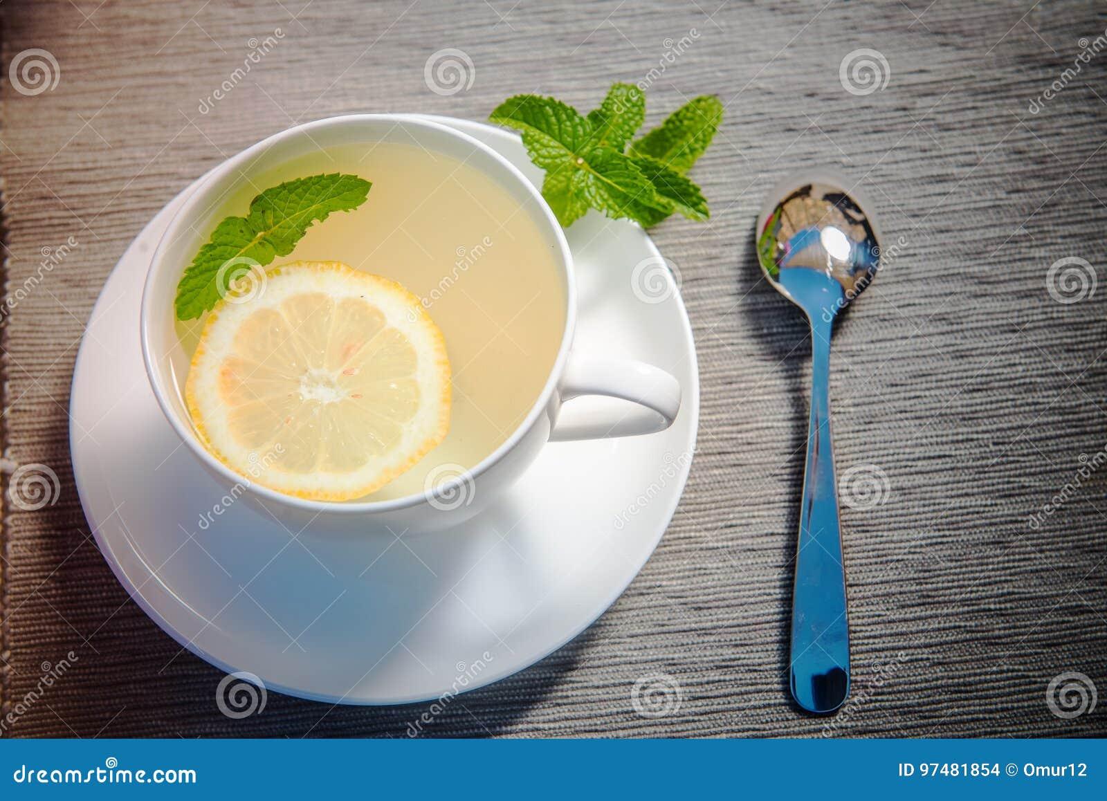 Limone e menta con la tazza di tè verde sulla tavola