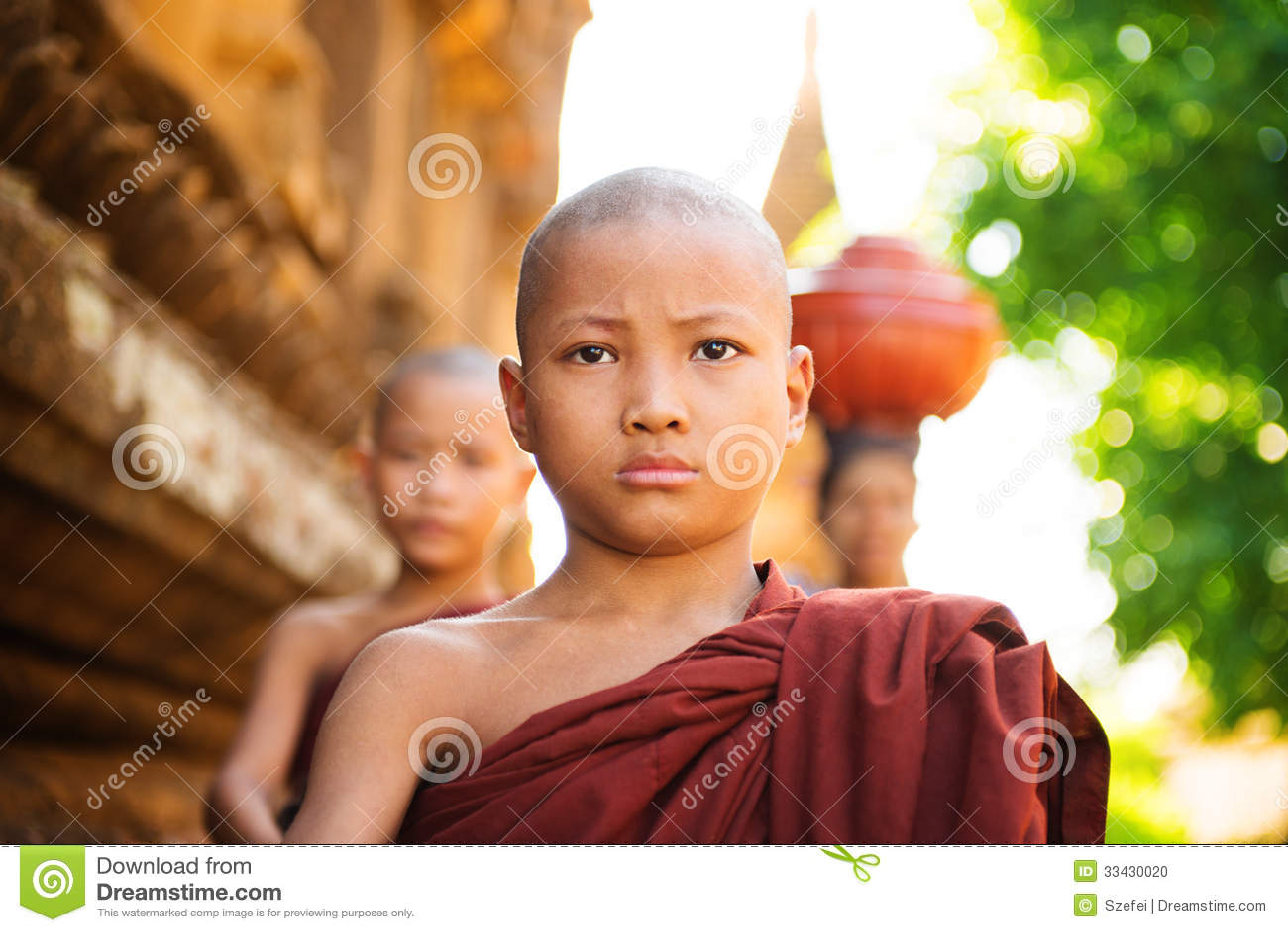 Limosnas jovenes de la mañana de los monjes que caminan budistas
