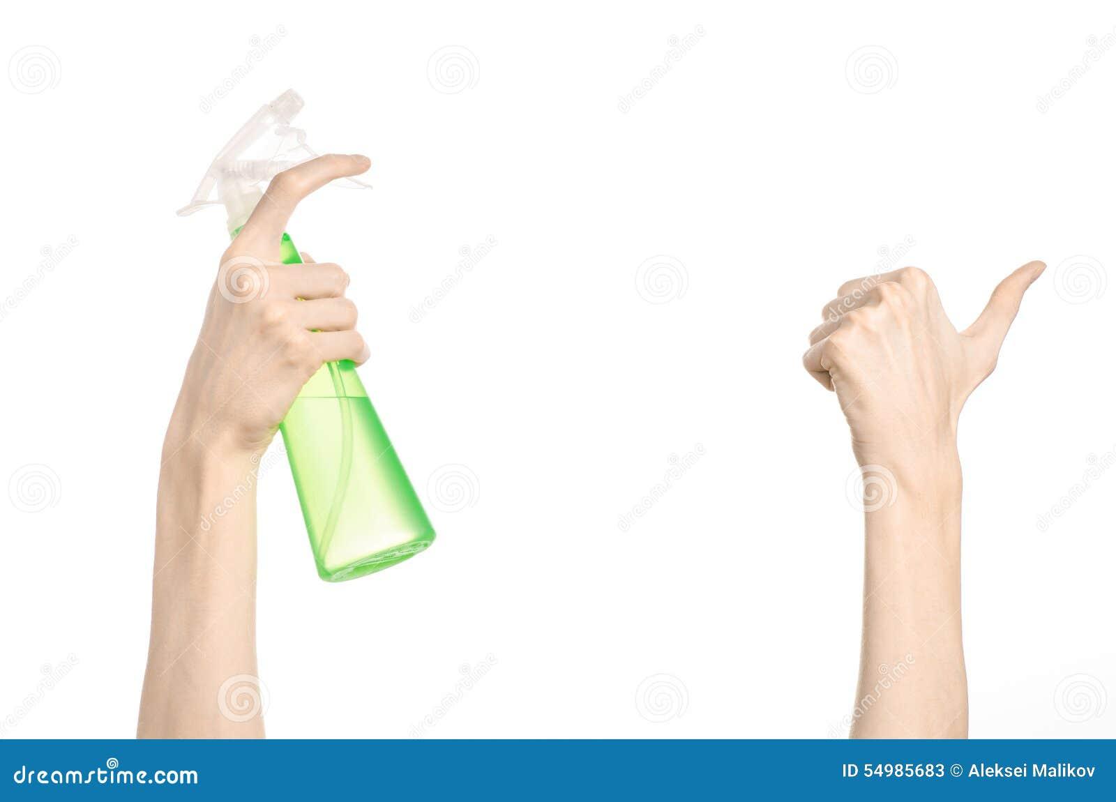 Limpando o tema da casa e do líquido de limpeza: a mão do homem que mantém uma garrafa verde do pulverizador para limpar isolada