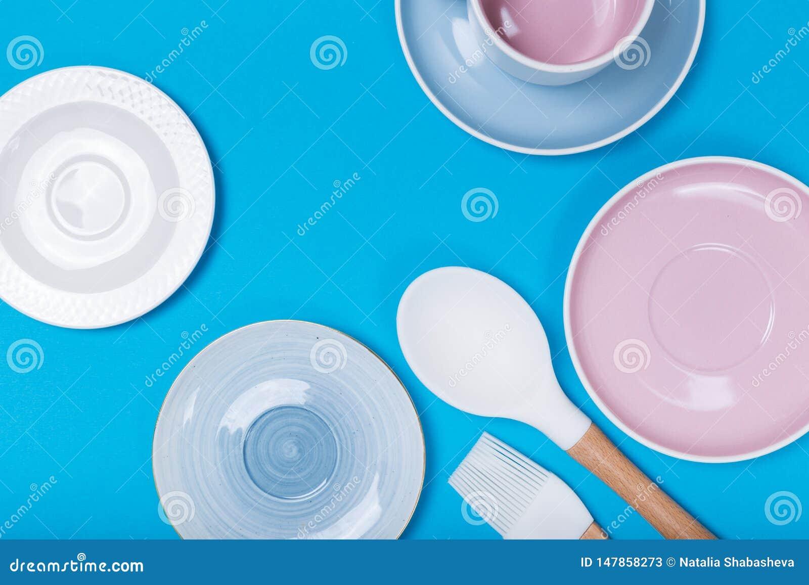 Limpe o grupo dos pratos, do caf? ou de ch? Abund?ncia de copos e de pires elegantes da porcelana no fundo azul