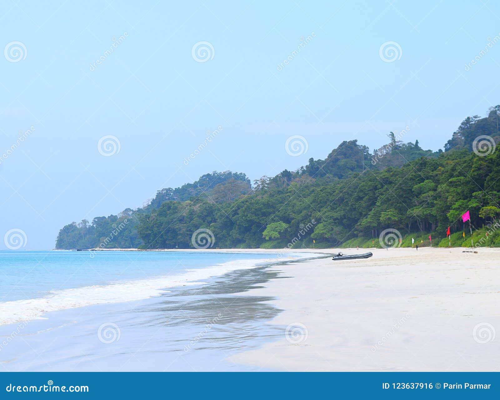 Limpe Sandy Beach branco, a água do mar azul, o céu claro, bandeiras coloridas, barco e o céu claro - praia de Radhanagar, ilha d