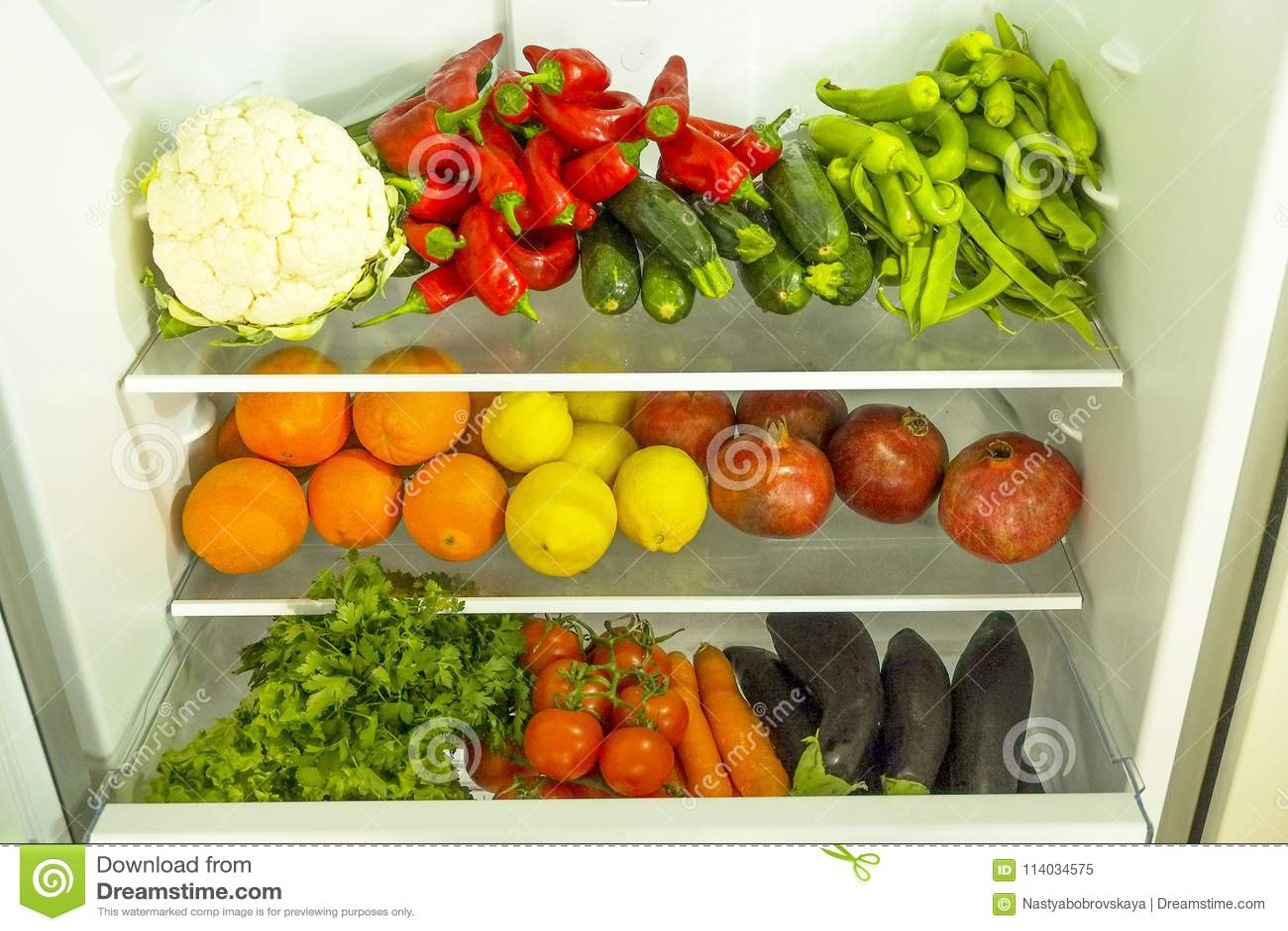 Limpie diversa mezcla de la verdura y de la fruta estacada en los estantes del refrigerador abierto Luz del día, productos orgáni