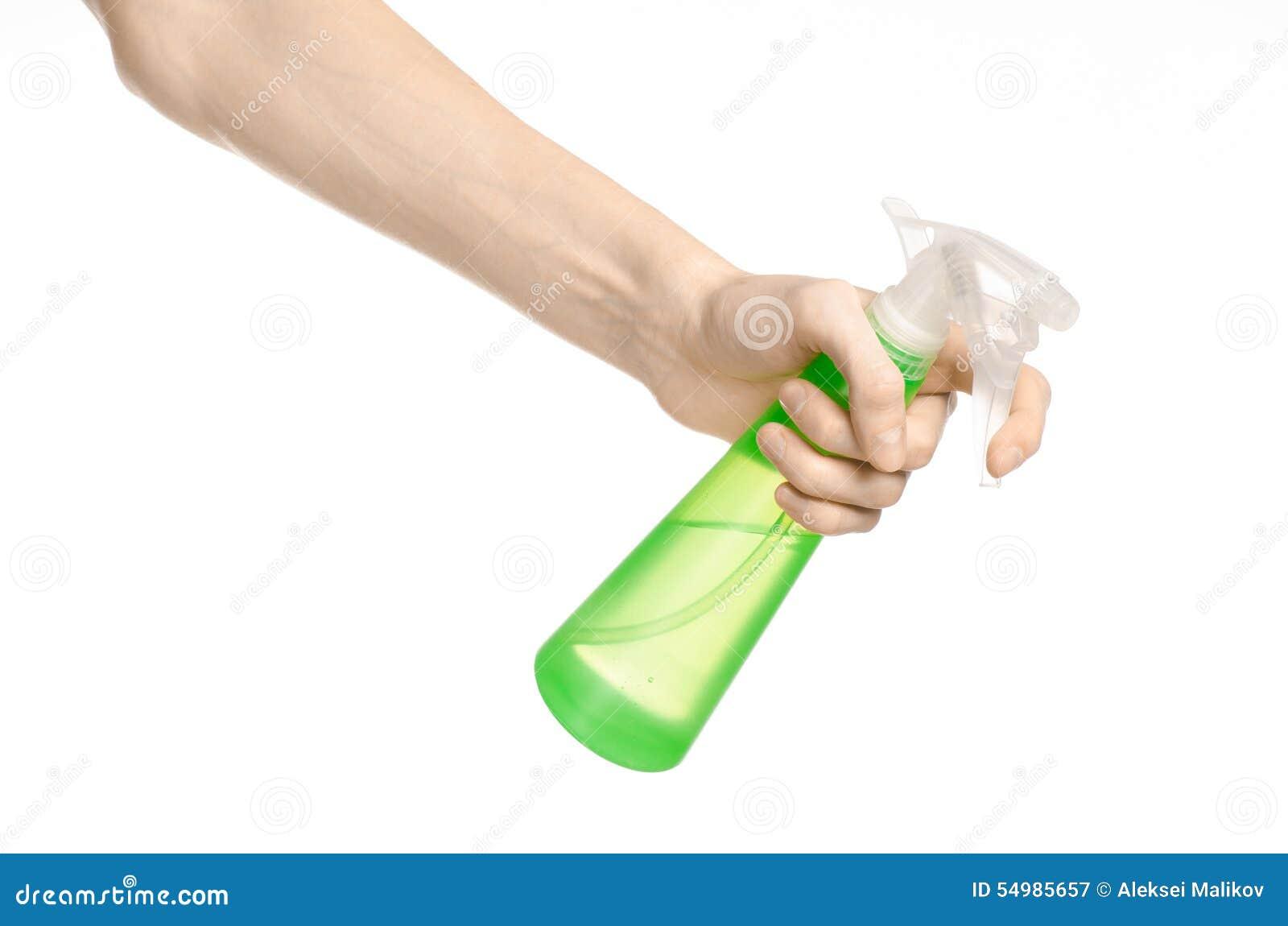 Limpieza del tema de la casa y del limpiador: la mano del hombre que sostiene una botella verde del espray para limpiar aislada e