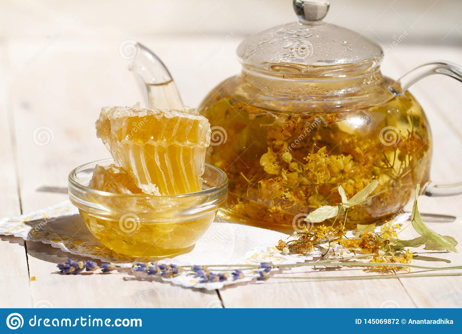 Linden lavender tea and dry linden and lavender flowers on white wooden table. Fresh Honey comb. glass teapot of herbal