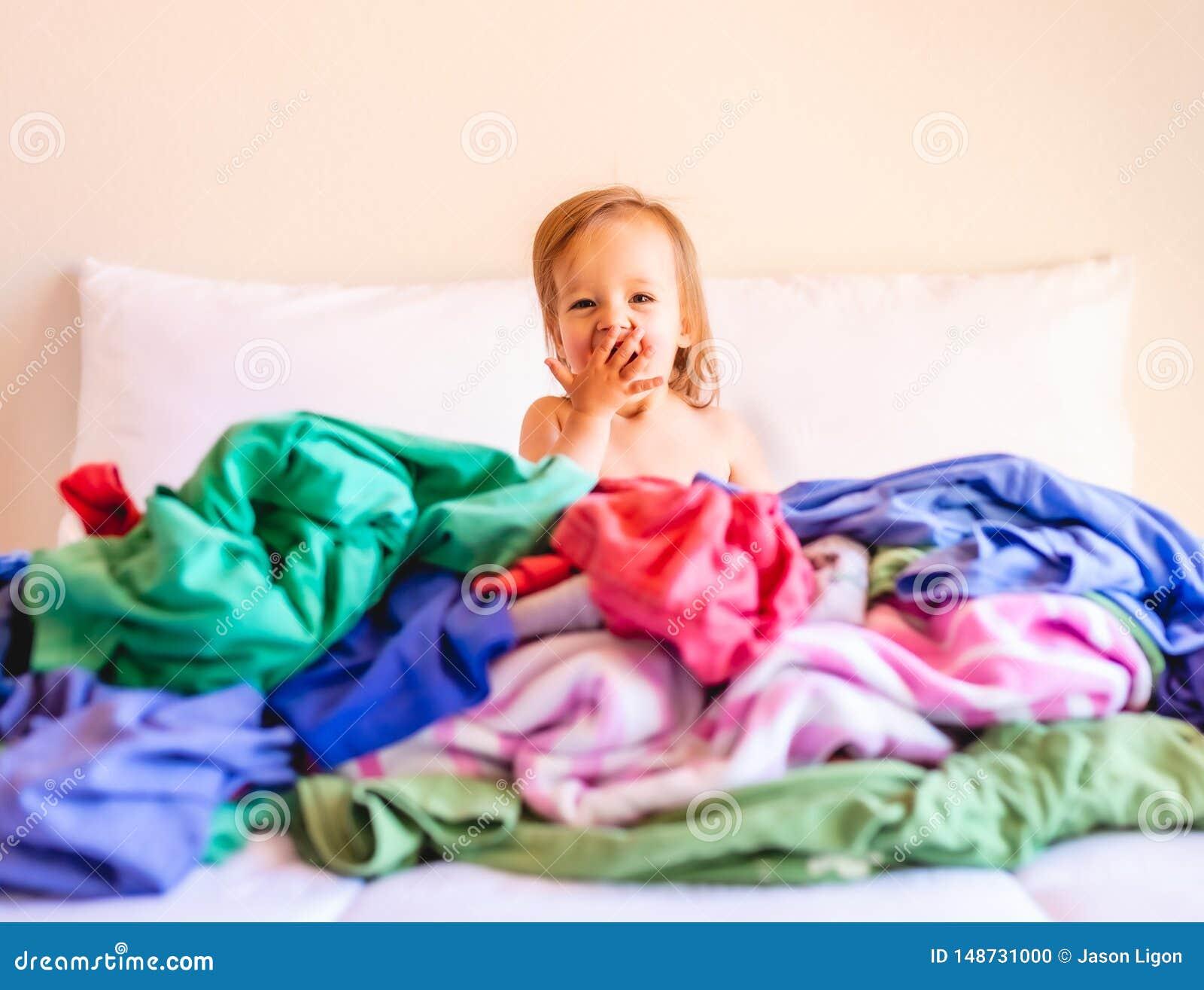 Lindo, adorable, sonriendo, beb? cauc?sico que se sienta en una pila de lavadero sucio en cama