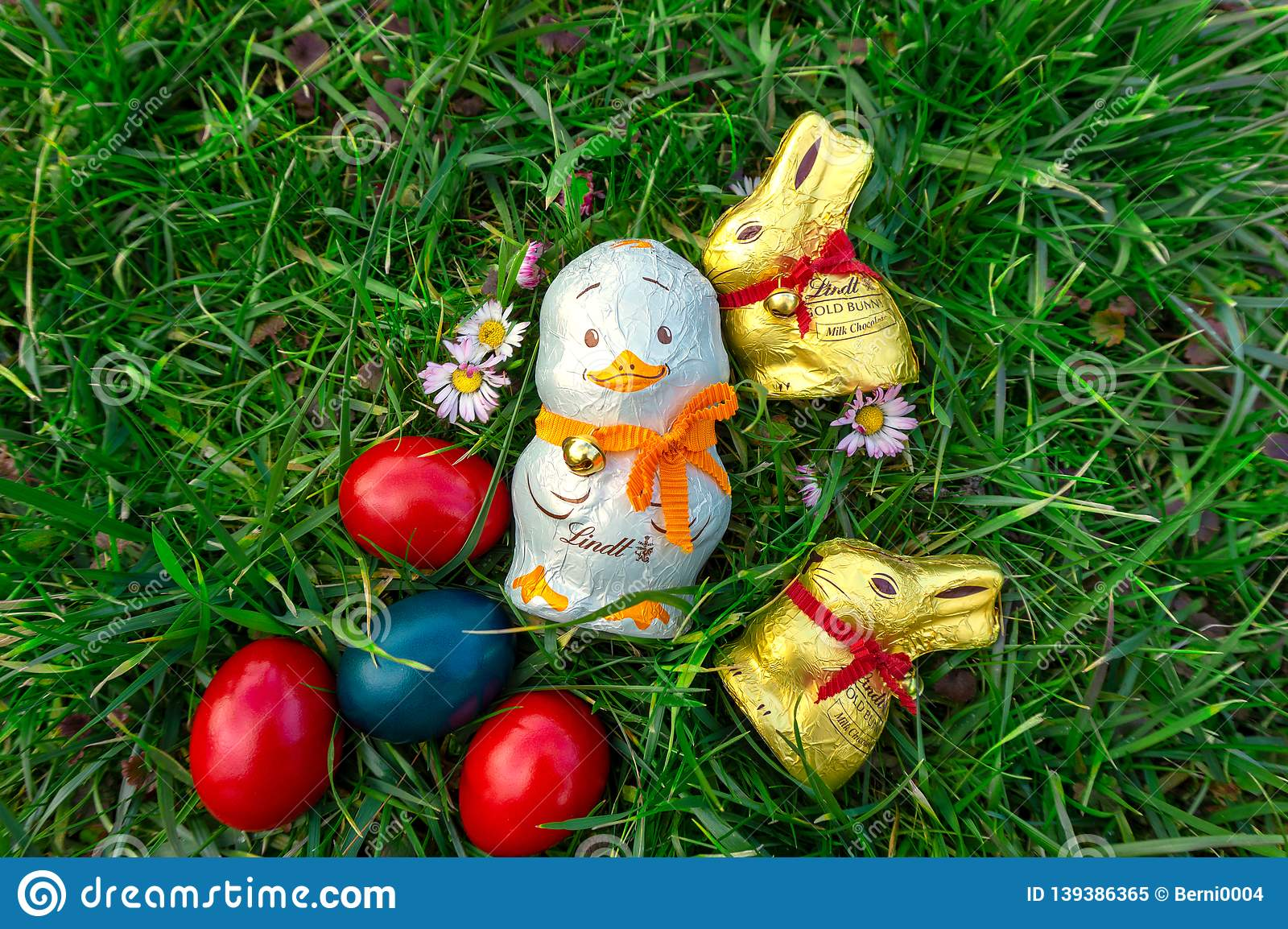 Lindt swiss golden milk chocolate bunny with red collar bell and a chocolate duck hidden in the grass Traditional chocolate on