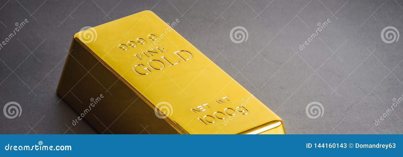 Lingote do lingote da barra de ouro em um fundo cinzento Localizado diagonalmente