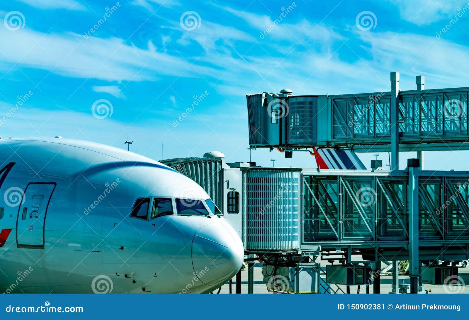 Linha aérea comercial estacionada na ponte do jato para o passageiro para decolar no aeroporto Ponte do embarque do passageiro do