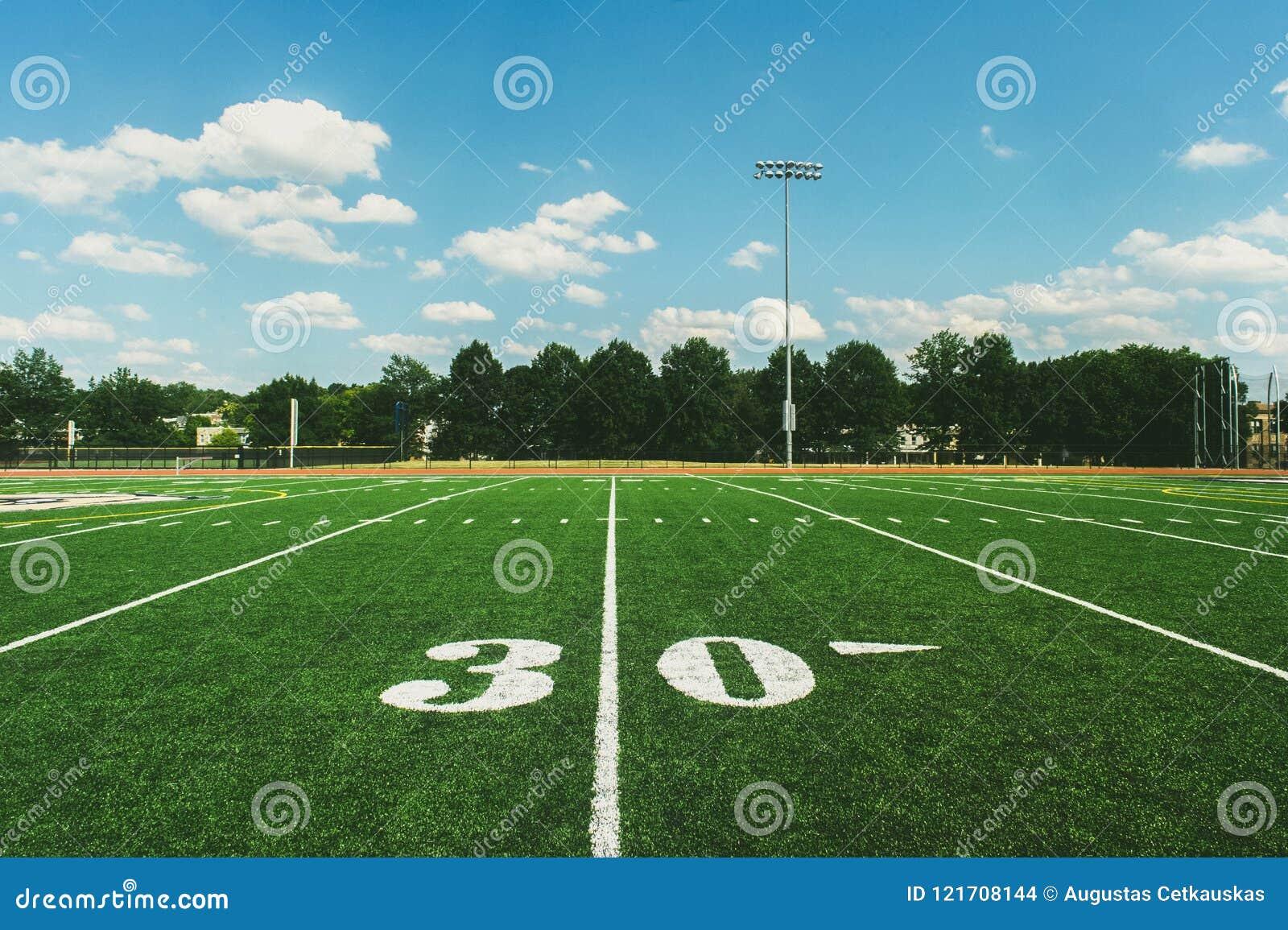 Linha de jardas 30 no campo de futebol americano e no céu azul