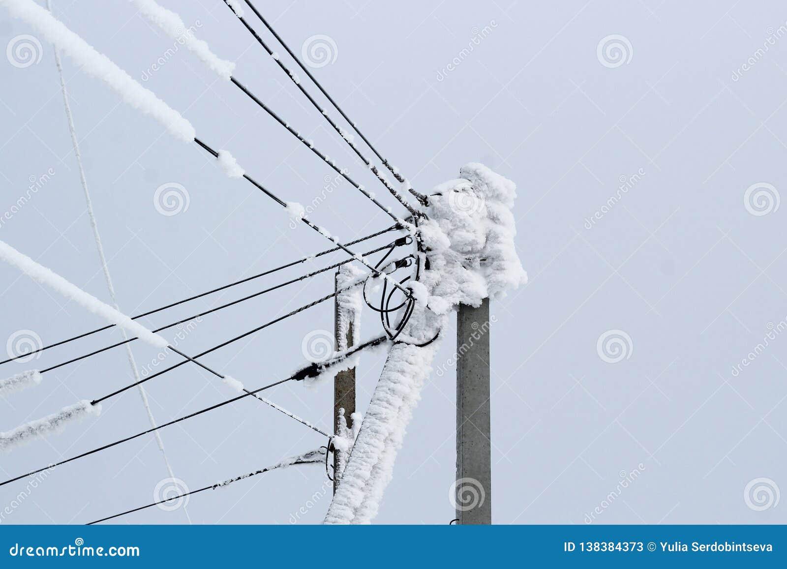 Linha elétrica em um polo de muitos fios cobertos com uma camada grossa de neve