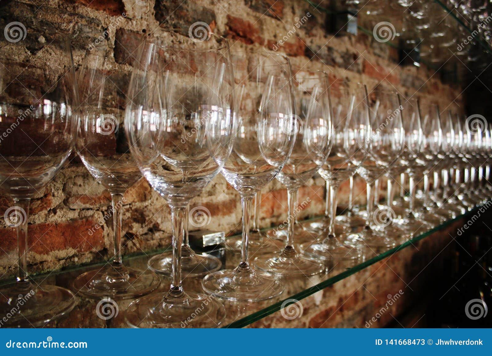 Linia okrzesani win szkła przed ścianą z cegieł w wino barze