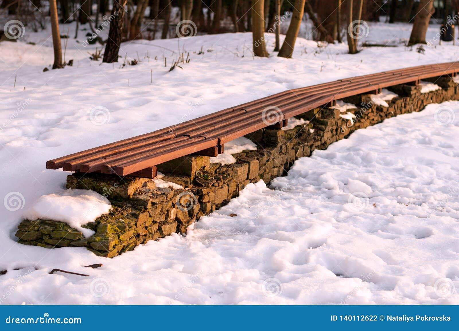 Linie der leeren Winterparkbank am sonnigen Tag Konzept von entspannen sich, Komfort, der verzierende Park, Frostwetter, schöne L