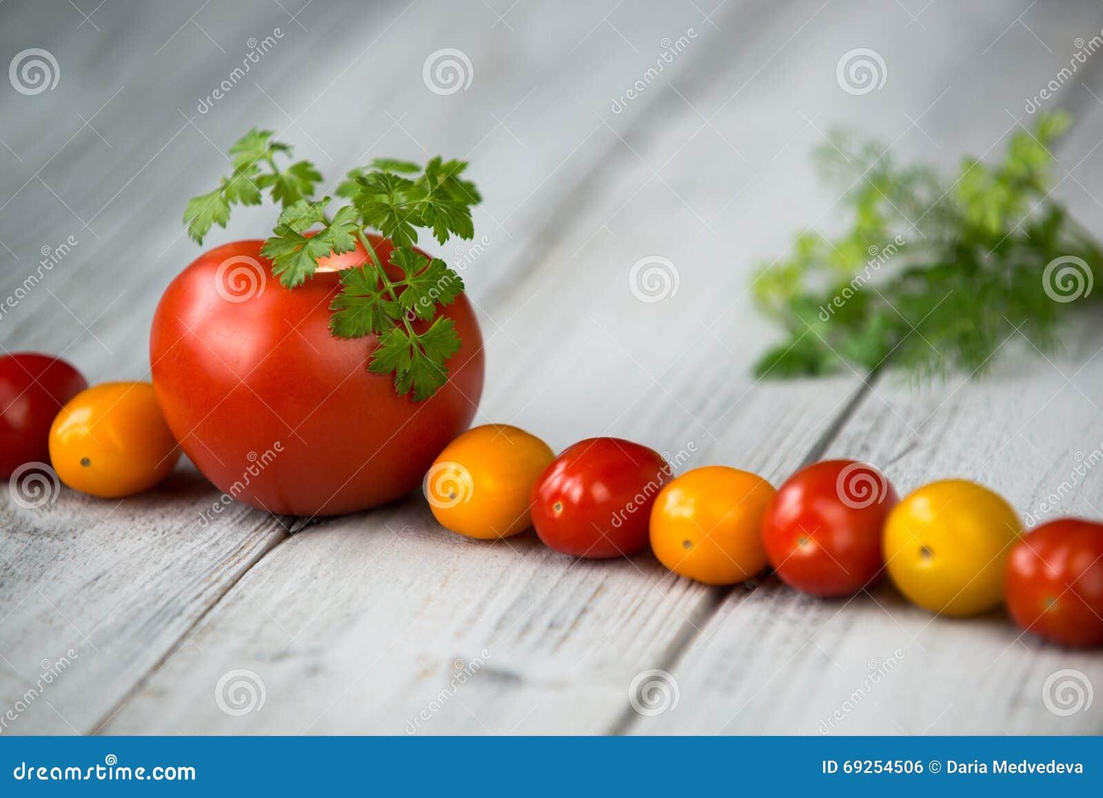 Linje av den naturliga organiska röda och gula körsbärsröda tomater och tomaten med ny persilja överst på en träbakgrund