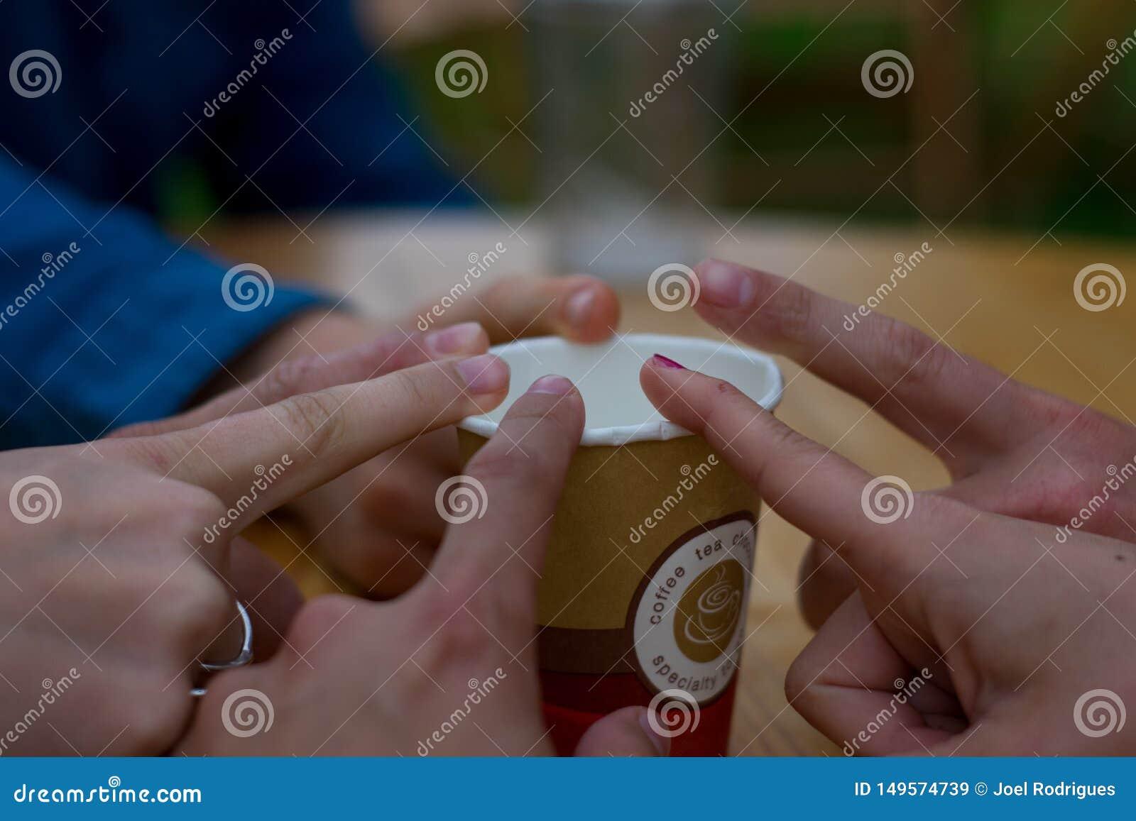 Linkebeek, B?lgica - 8 de junho de 2018: Grupo de amigos que tocam no dedo no copo de caf?